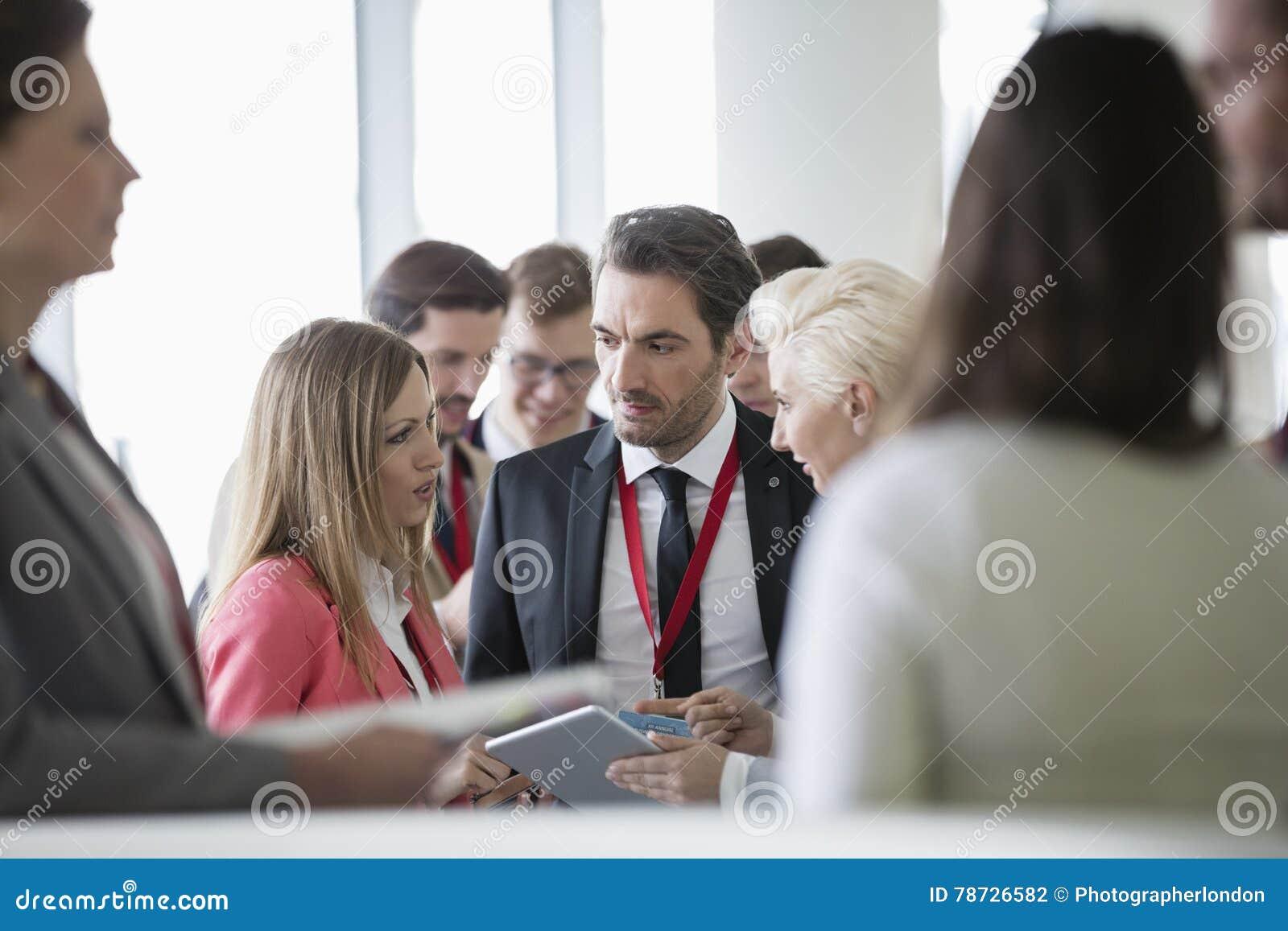 Affärsfolk som diskuterar över den digitala minnestavlan i konventcentrum