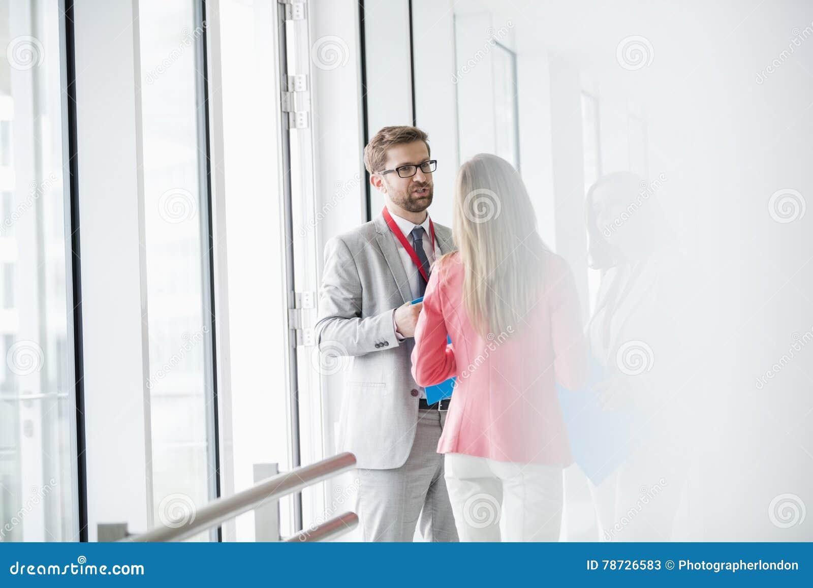 Affärsfolk som diskuterar i ljust tänd konventcentrum