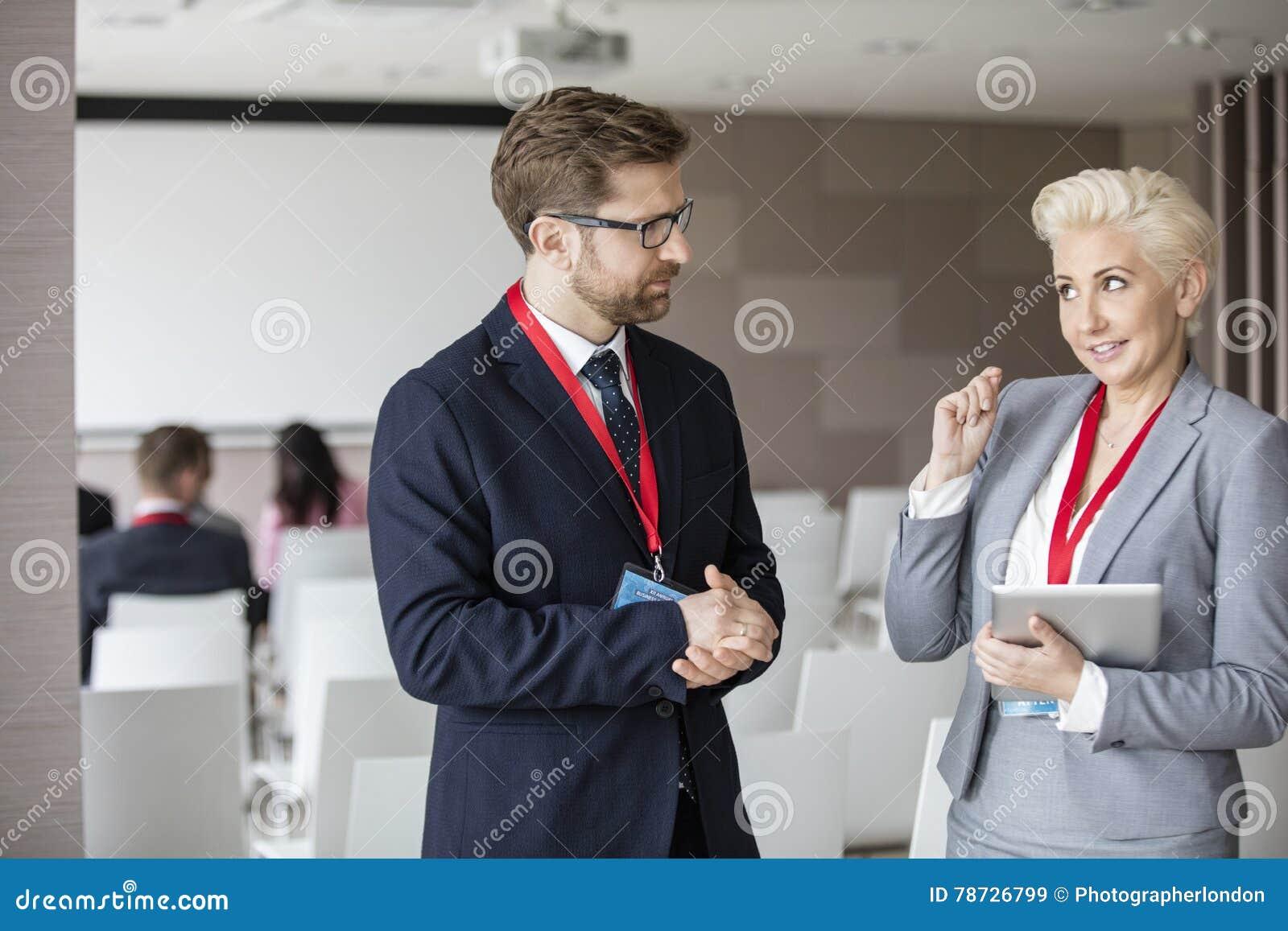 Affärsfolk som diskuterar i seminariumkorridor