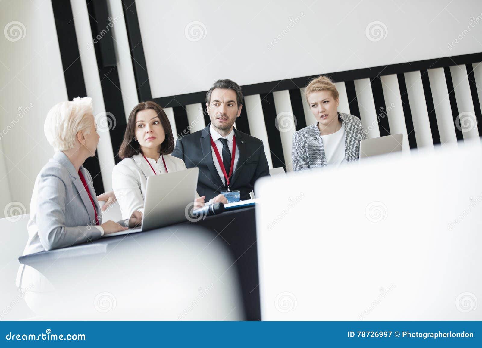 Affärsfolk som diskuterar, medan sitta på skrivbordet i seminariumkorridor