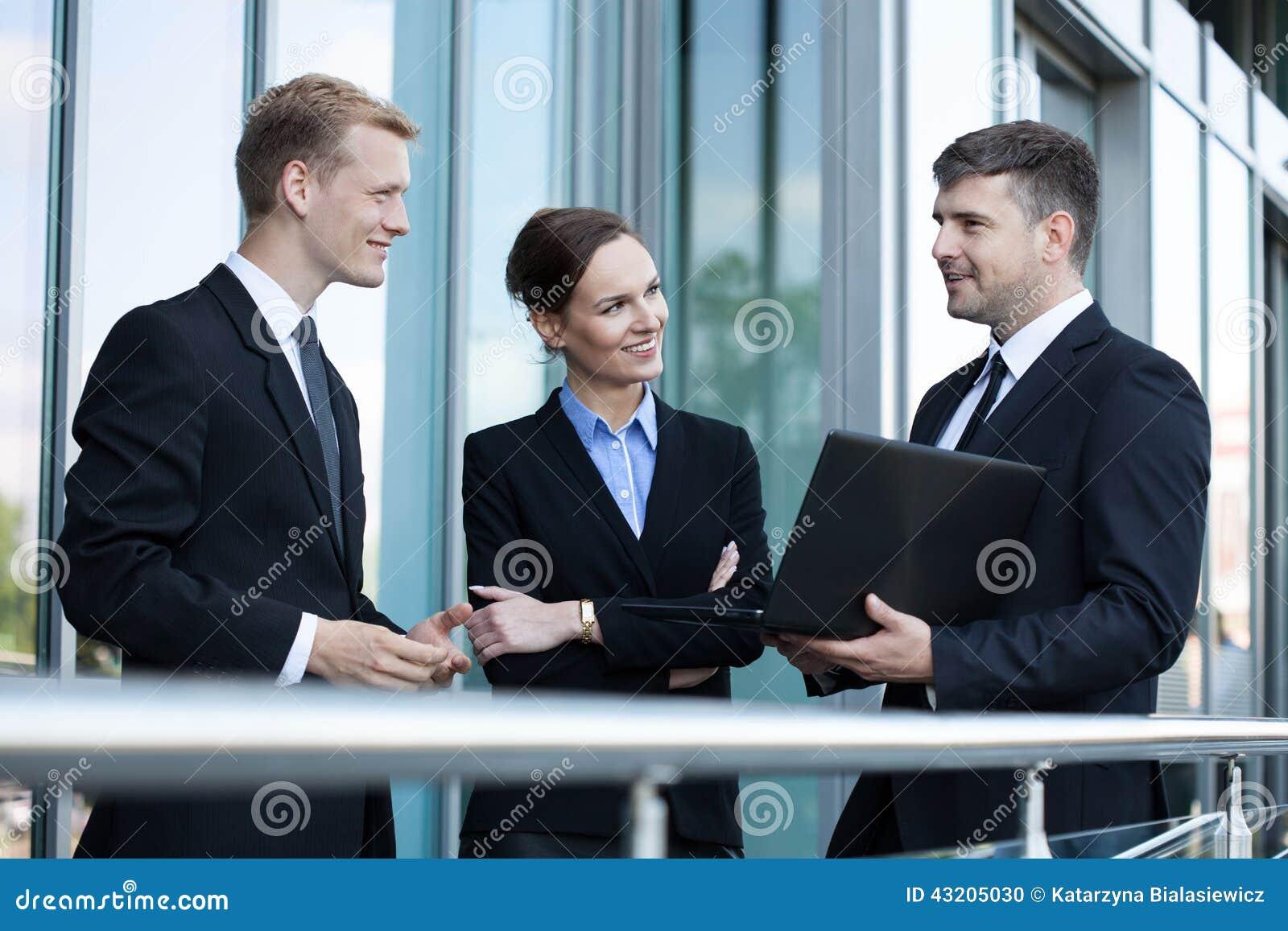 Affärsfolk som framme talar av kontorsbyggnad