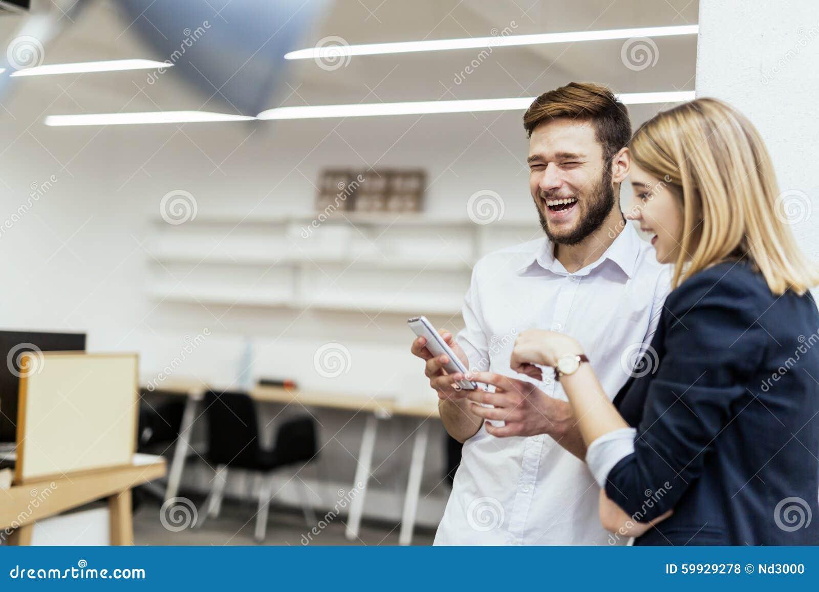 Affärsfolk som har gyckel under avbrott i ett kontor