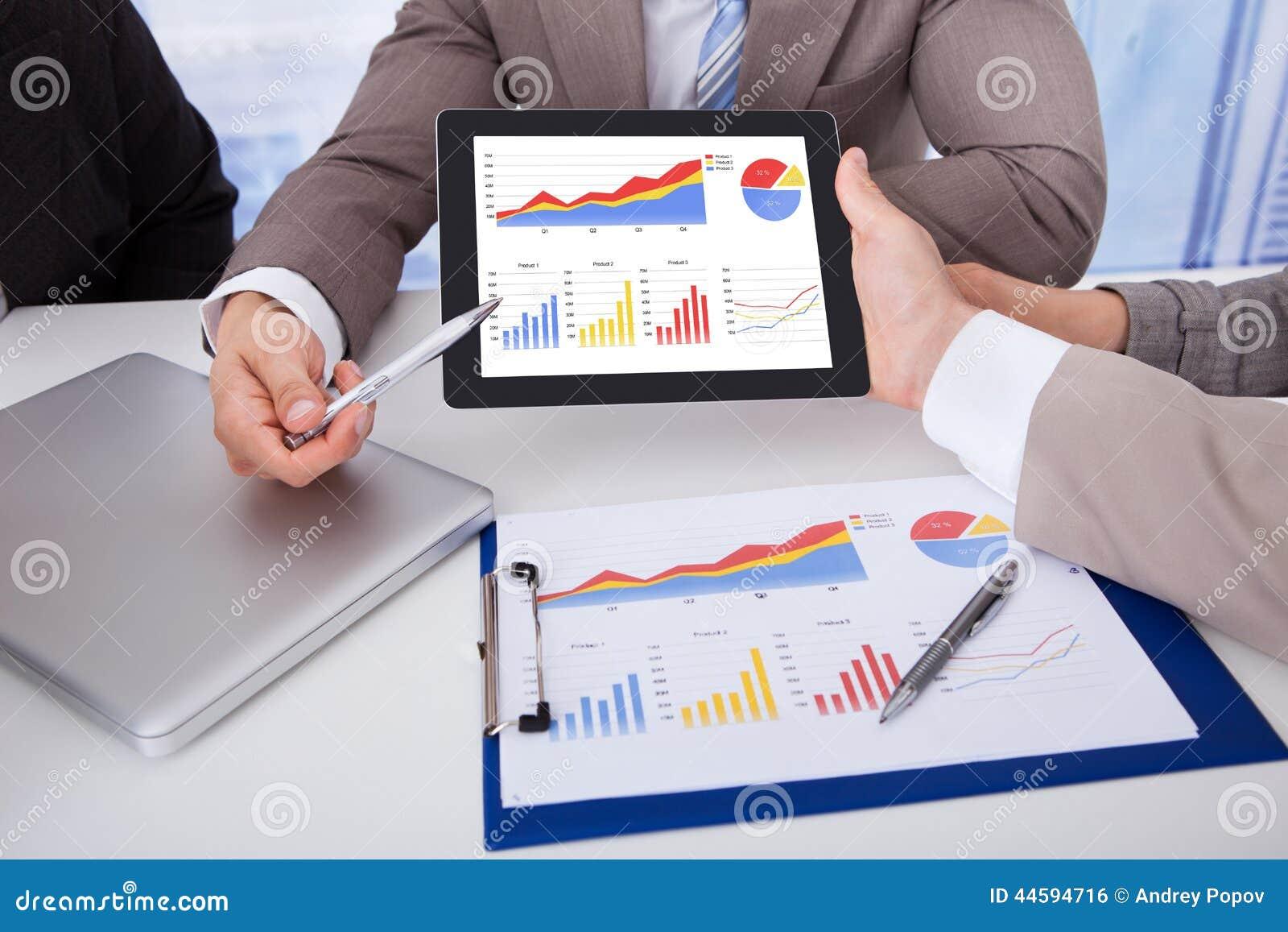 Affärsfolk som i regeringsställning diskuterar grafen på den digitala minnestavlan