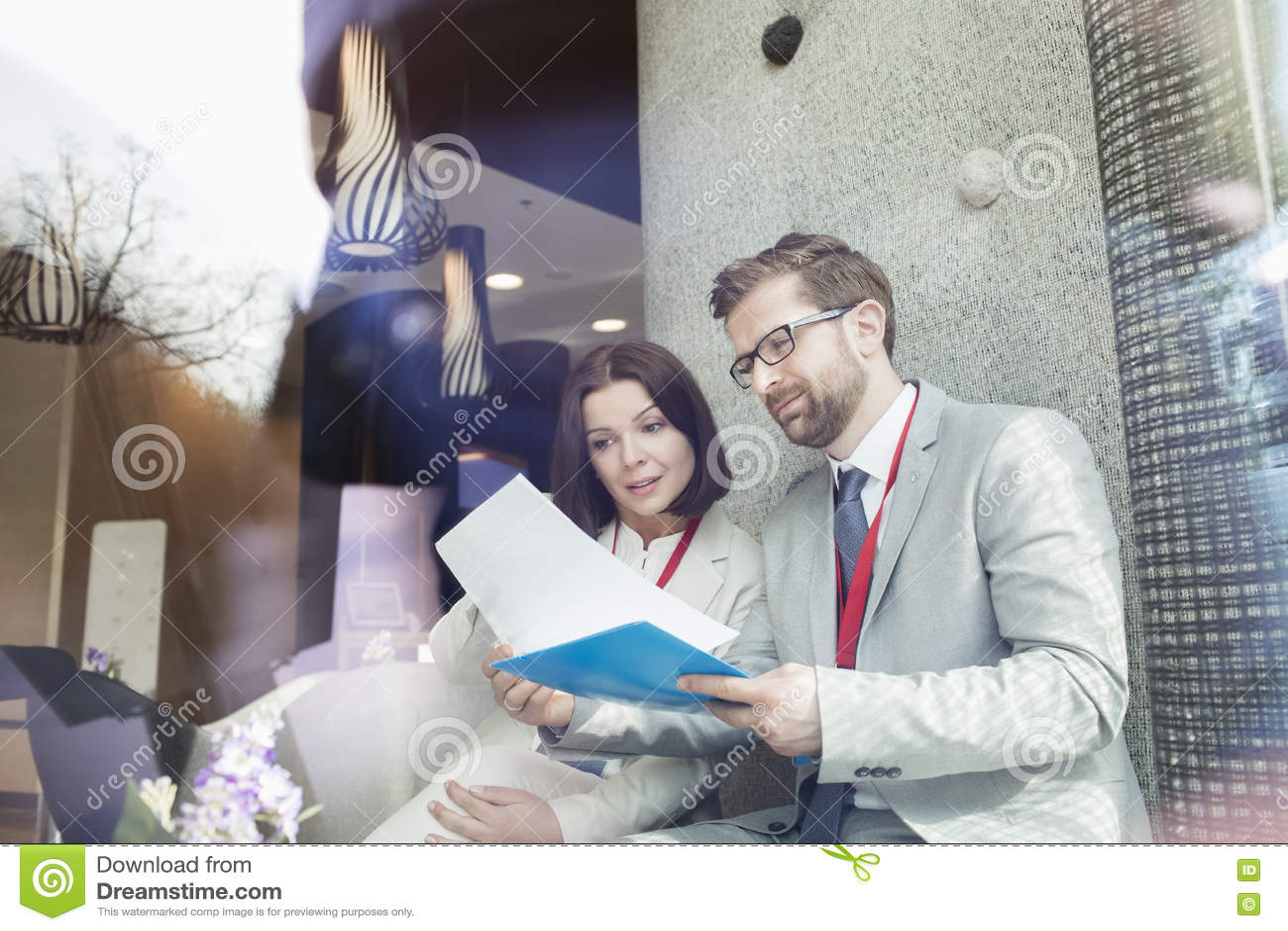 Affärsfolk som läser dokumentet, medan sitta i konventcentrum