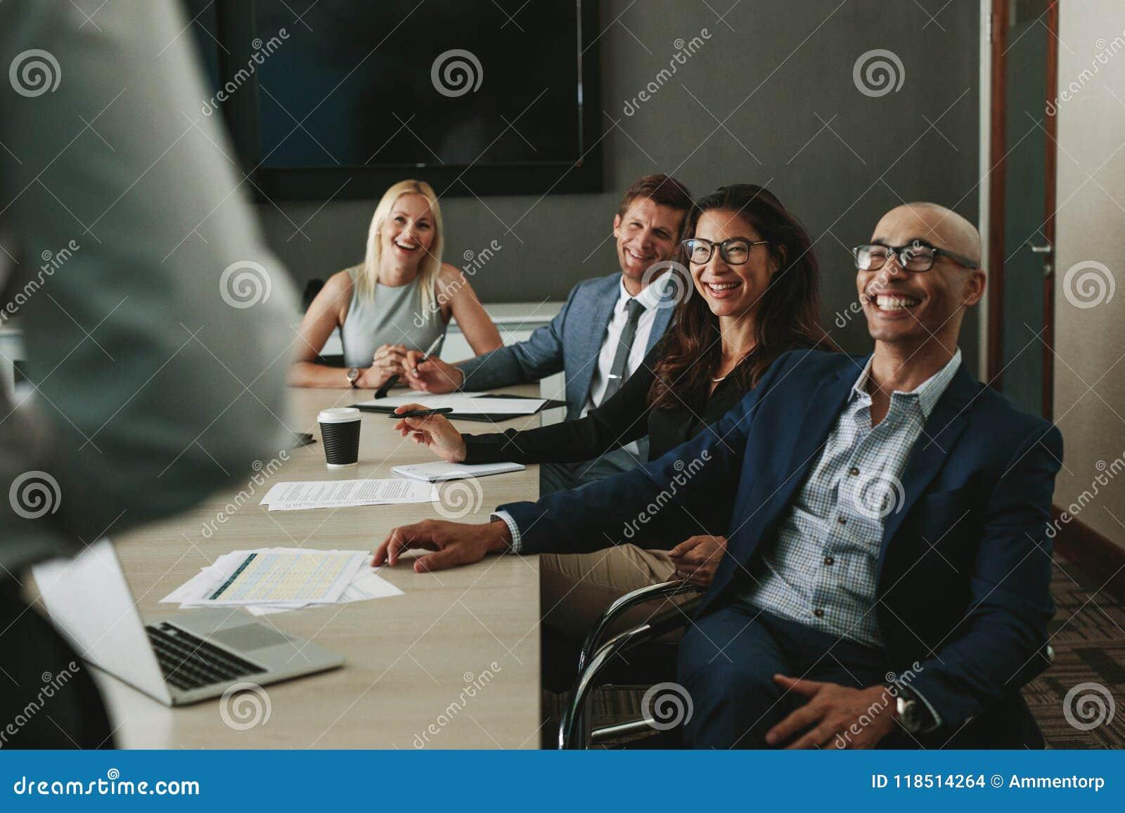 Affärsfolk som ler under möte i bräderum