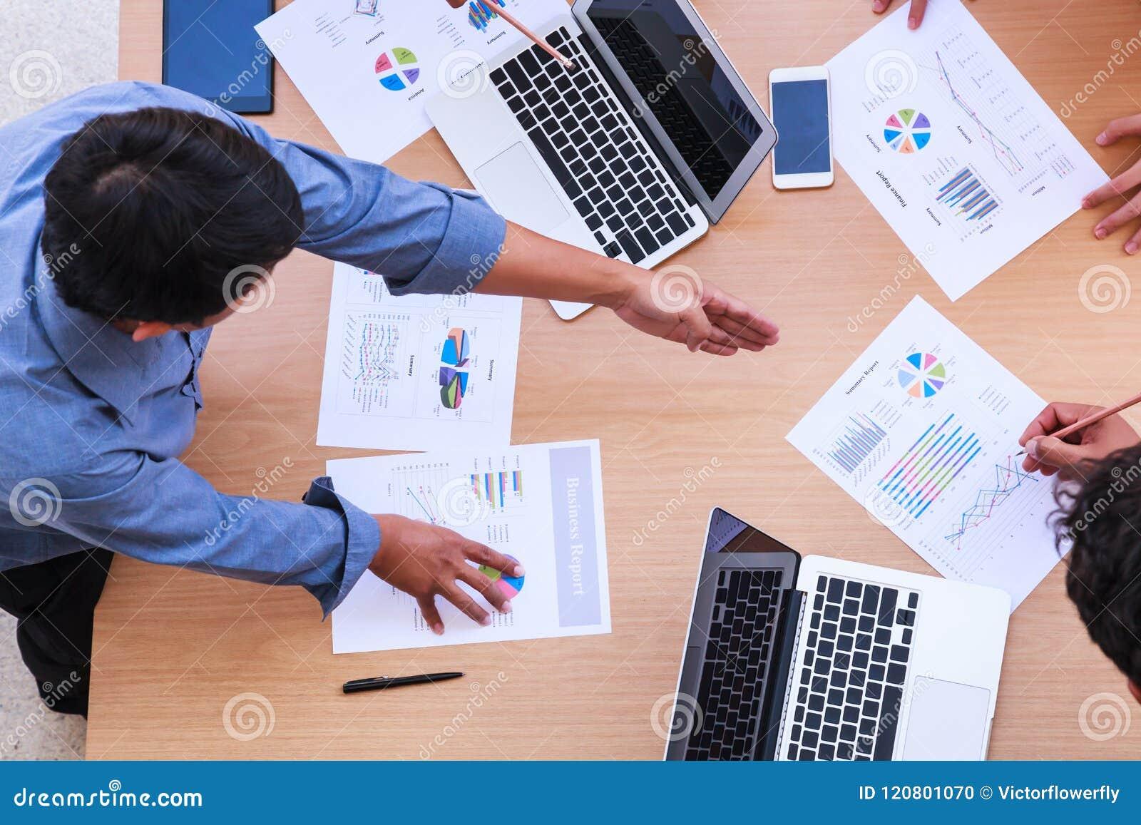 Affärsfolk som möter i kontorsbegreppet, genom att använda idéer, diagram, datorer, minnestavla, smarta apparater på affärsplanlä