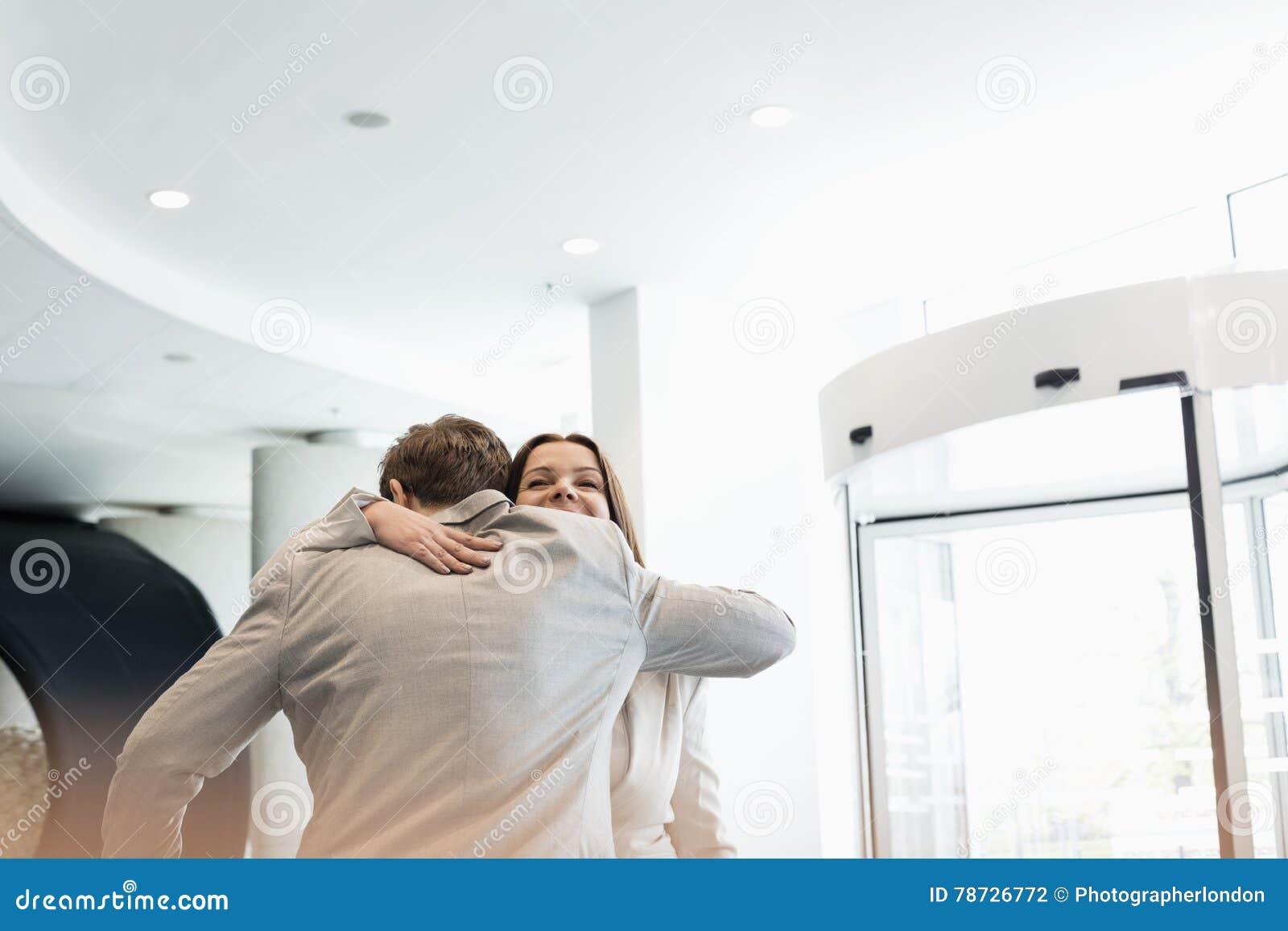 Affärsfolk som omfamnar på den ljust tända konventcentret