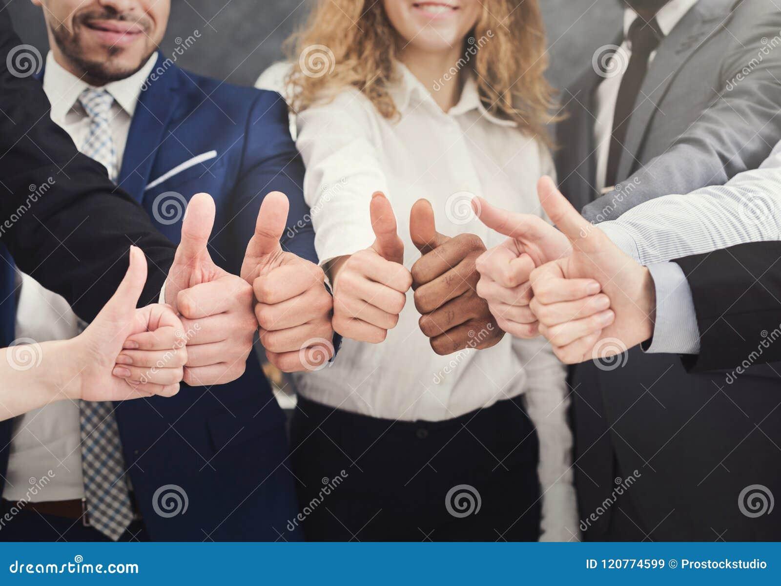 Affärsfolk som rymmer upp många tummar