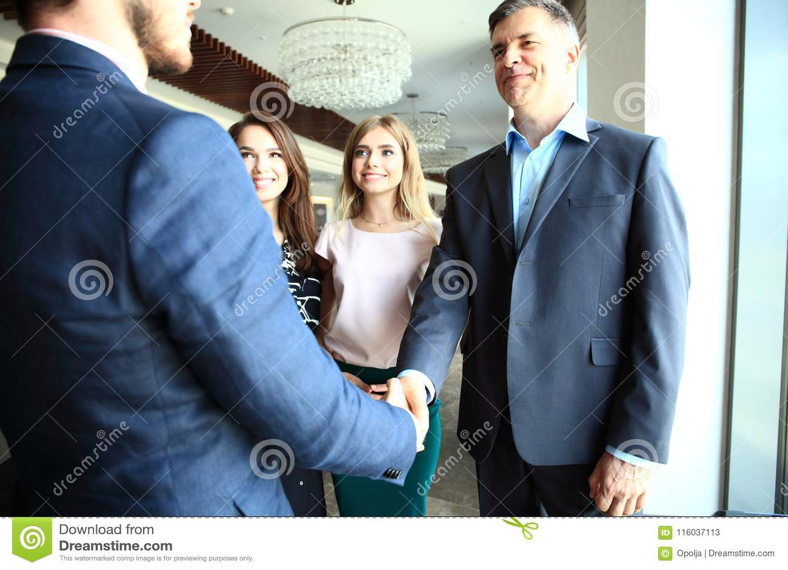 Affärsfolk som skakar händer, fulländande övre ett möte