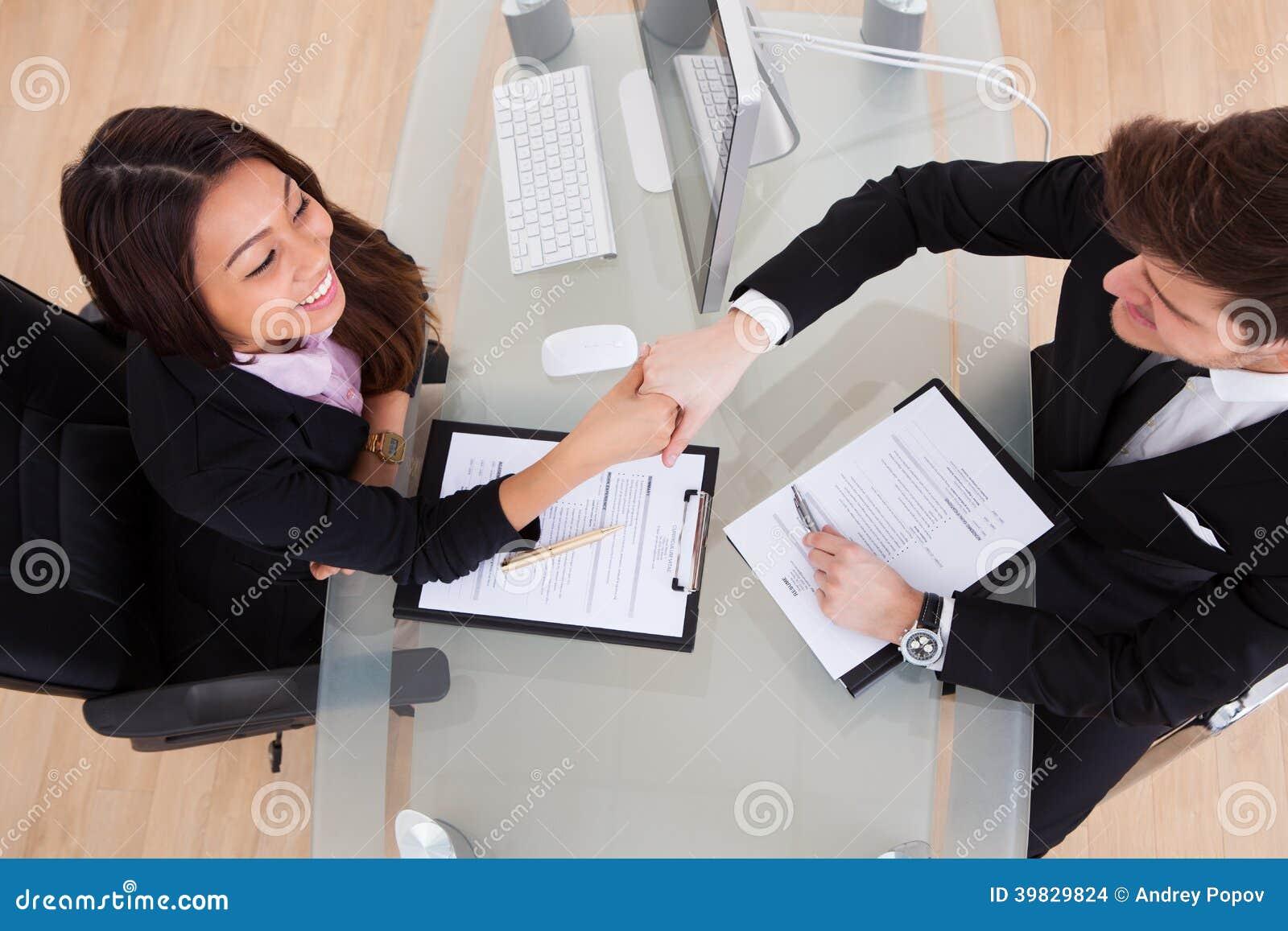 Affärsfolk som skakar händer på skrivbordet