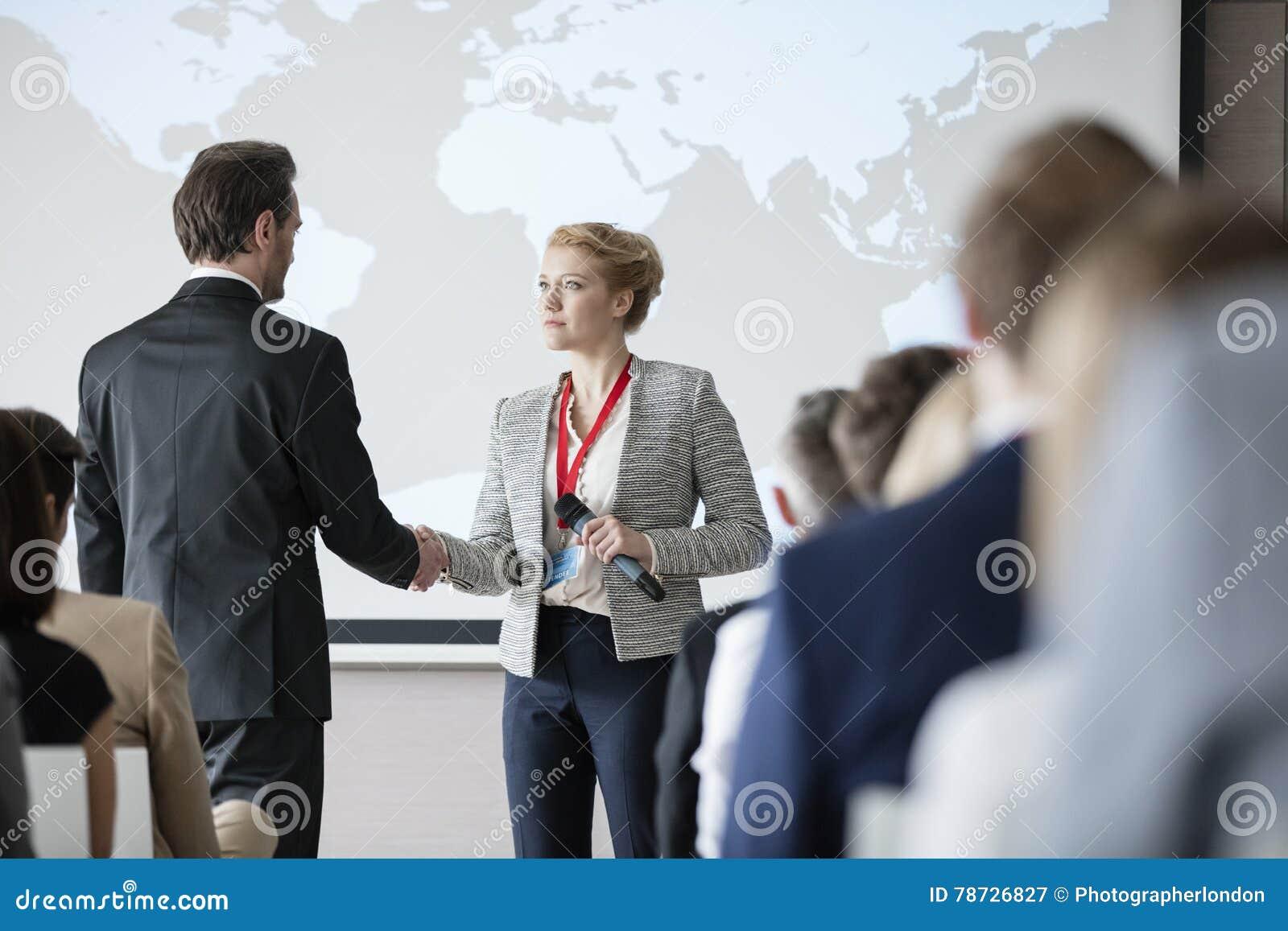 Affärsfolk som skakar händer under seminarium
