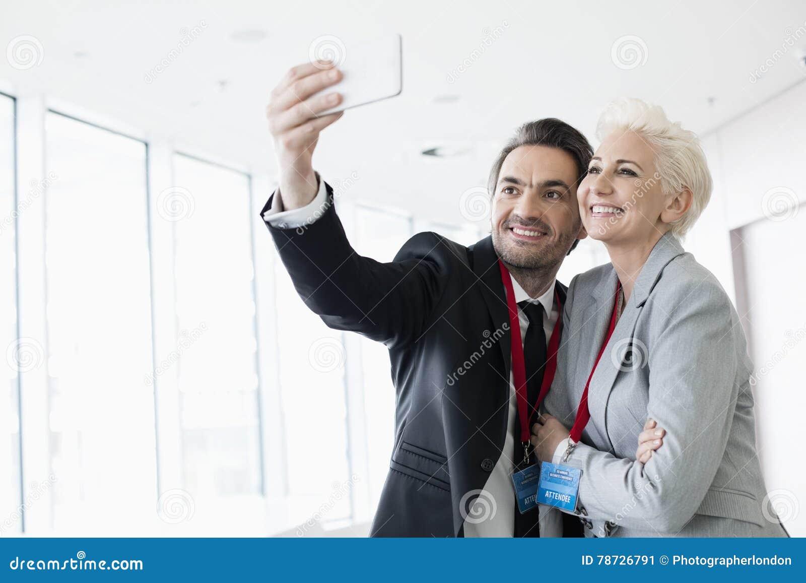 Affärsfolk som tar selfie i konventcentrum