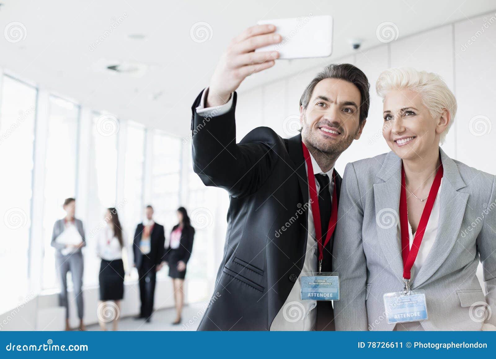 Affärsfolk som tar selfie i konventcentrum med kollegor som går i bakgrund