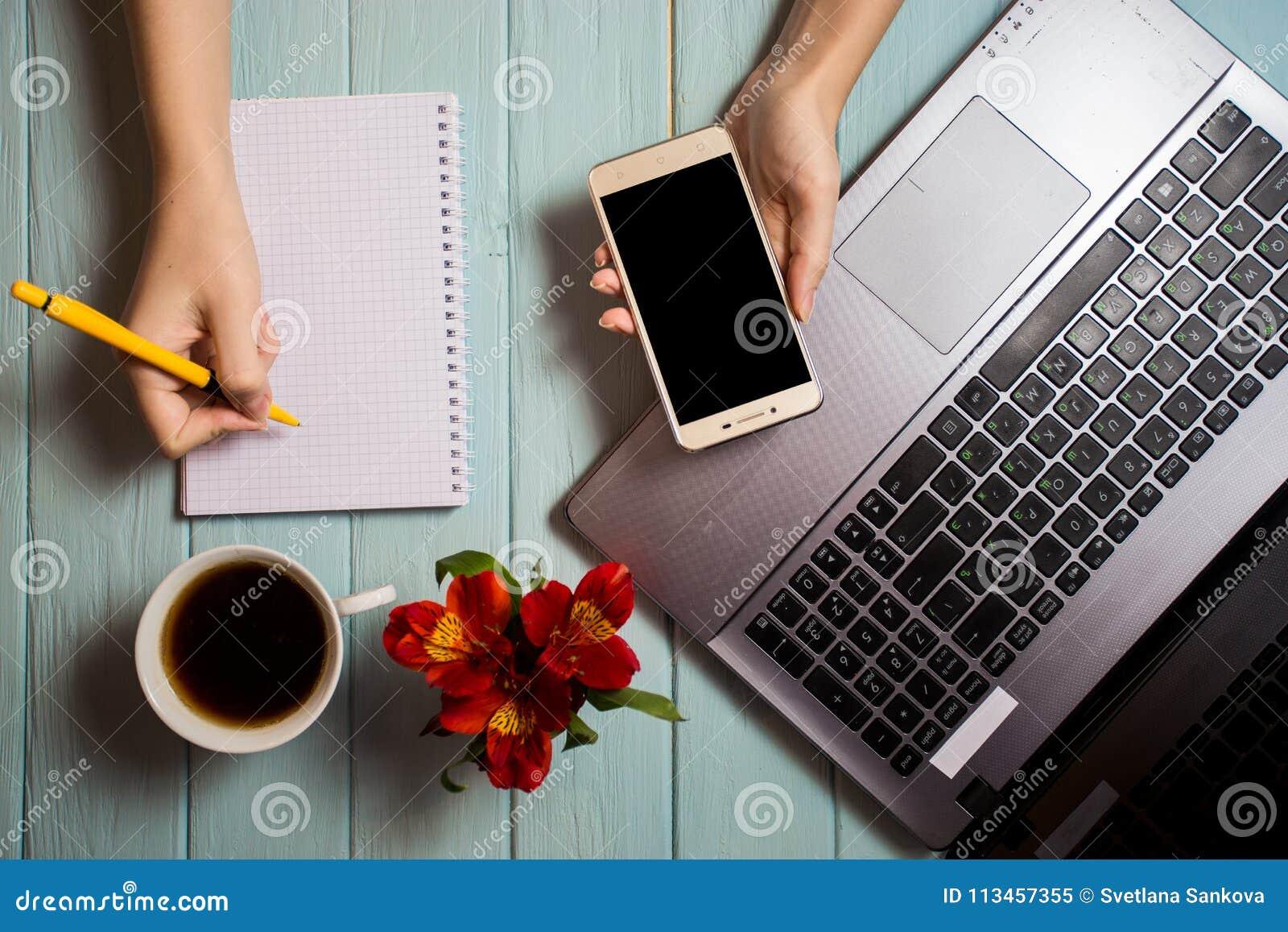 Affärshandkvinna som använder datoren och skriver på den tomma anteckningsboken med telefonen