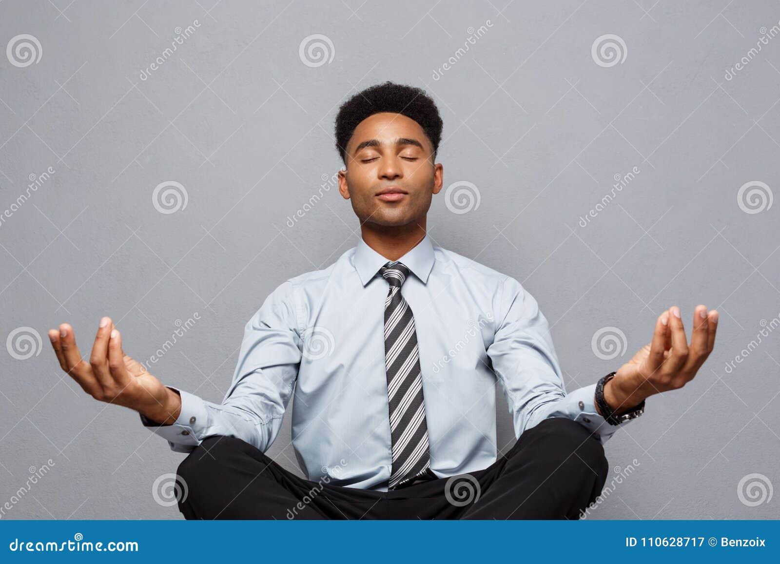 Affärsidé - stående av afrikansk amerikanaffärsmannen som gör meditation och yoga, in innan att arbeta