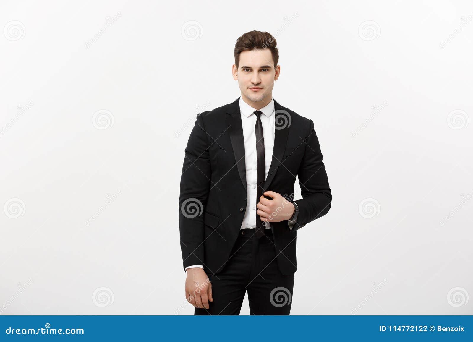 Affärsidé: Ung stilig grabb för stiligt leende för man lyckligt i den smarta dräkten som poserar över Grey Background