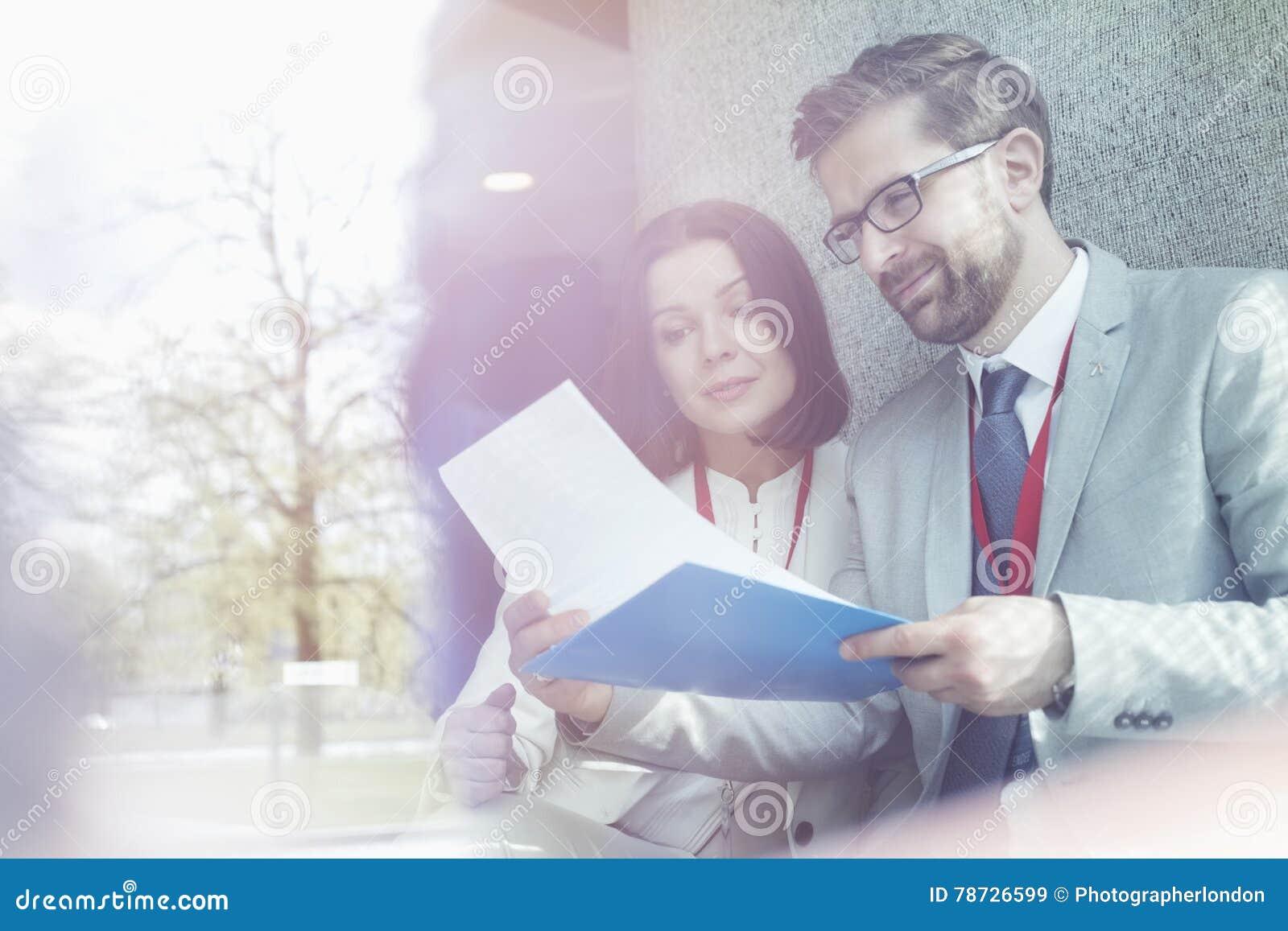Affärskollegor som läser dokumentet, medan sitta i konventcentrum