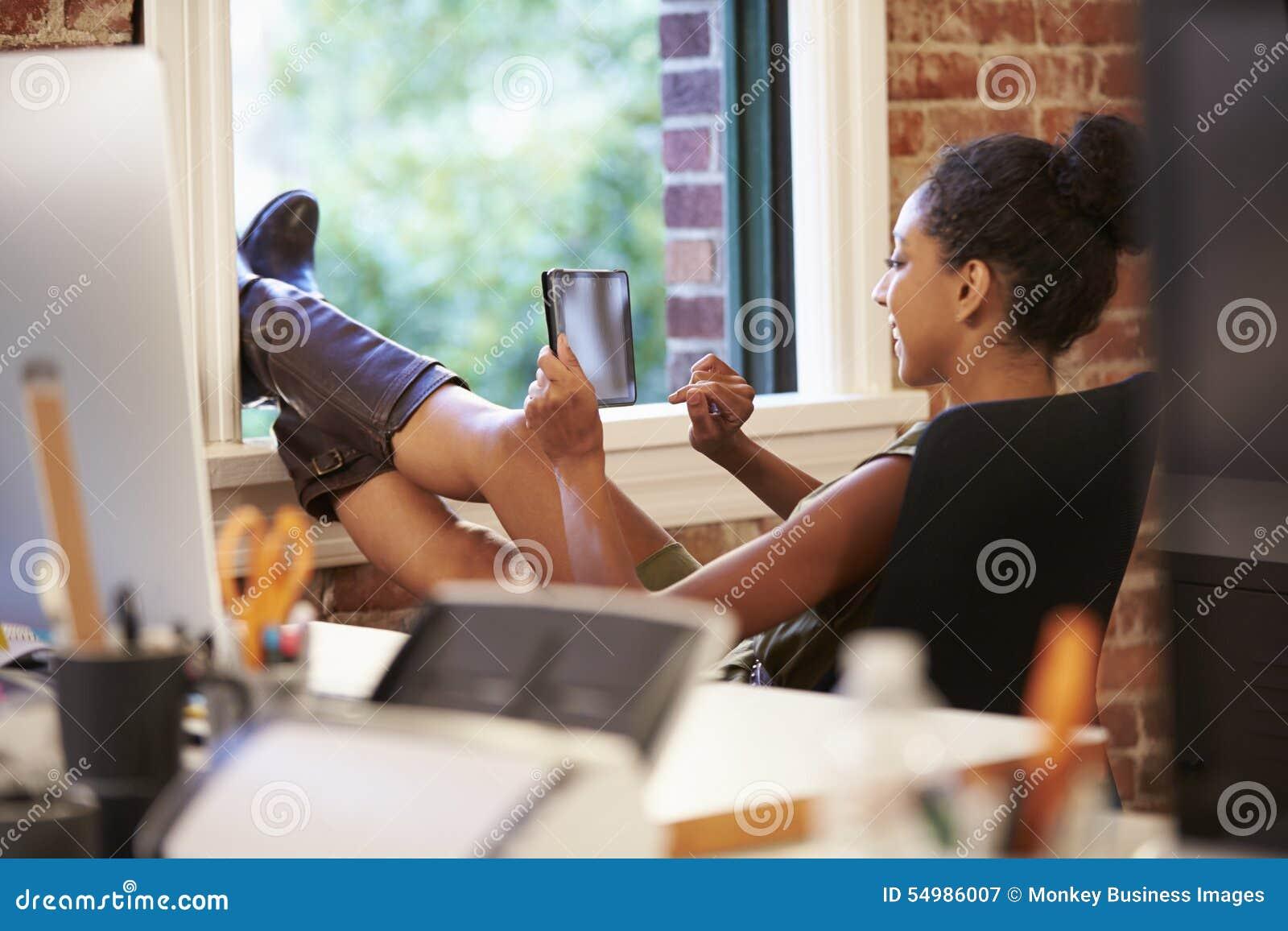 Affärskvinna With Digital Tablet som kopplar av i modernt kontor