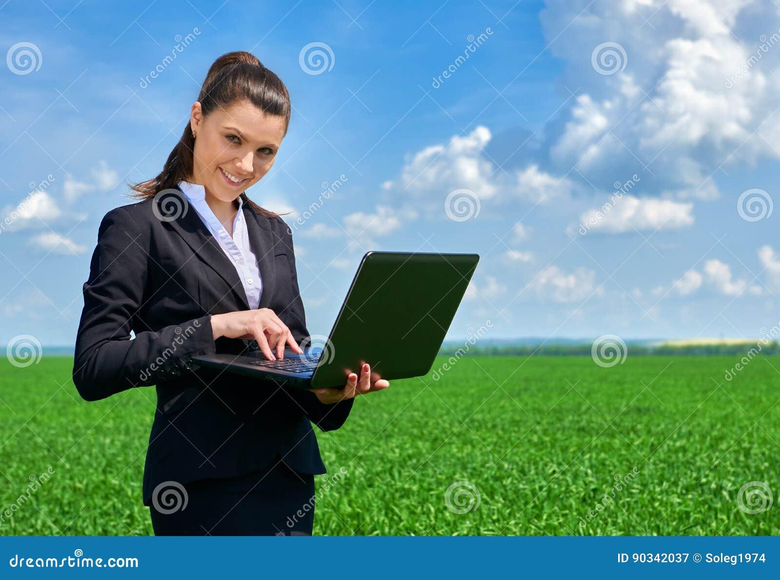 Affärskvinna i arbete för fält för grönt gräs utomhus- på bärbara datorn Iklädd svart dräkt för ung flicka Härligt vårlandskap me