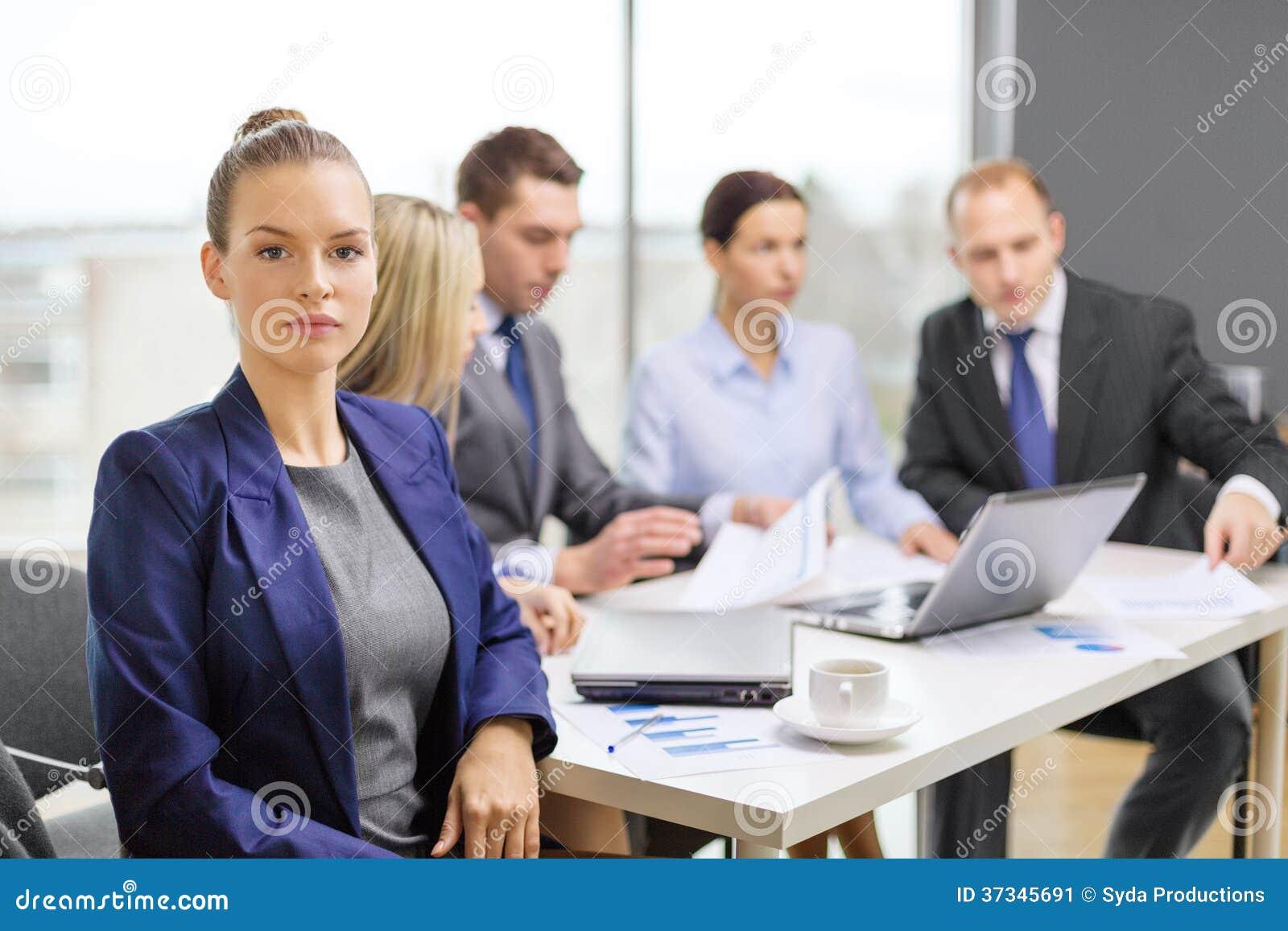 Affärskvinna i regeringsställning med laget på baksidan