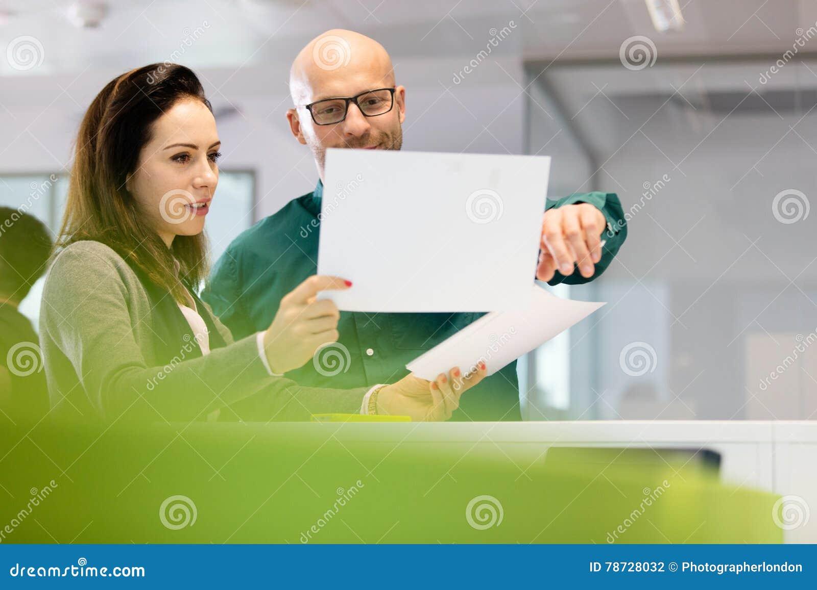 Affärskvinna med den manliga kollegan som i regeringsställning diskuterar över dokument