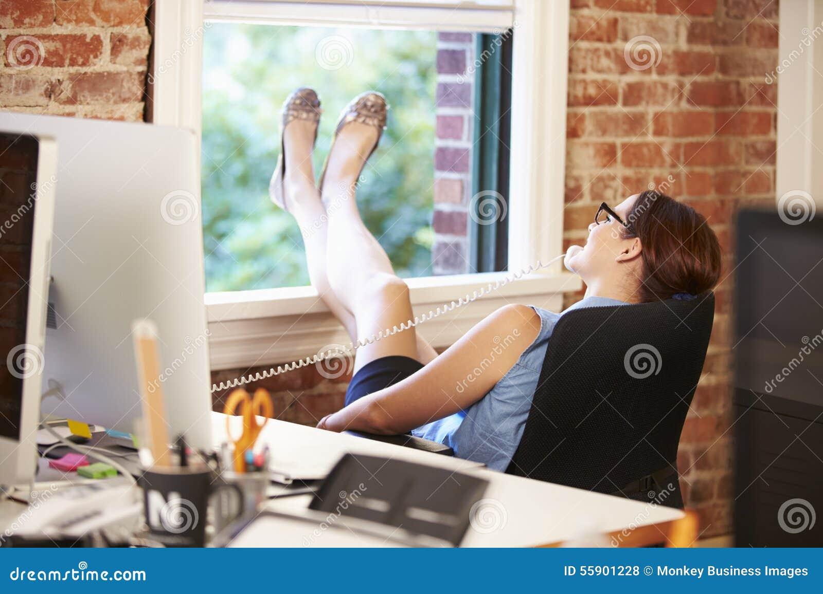 Affärskvinna On Phone Relaxing i modernt idérikt kontor