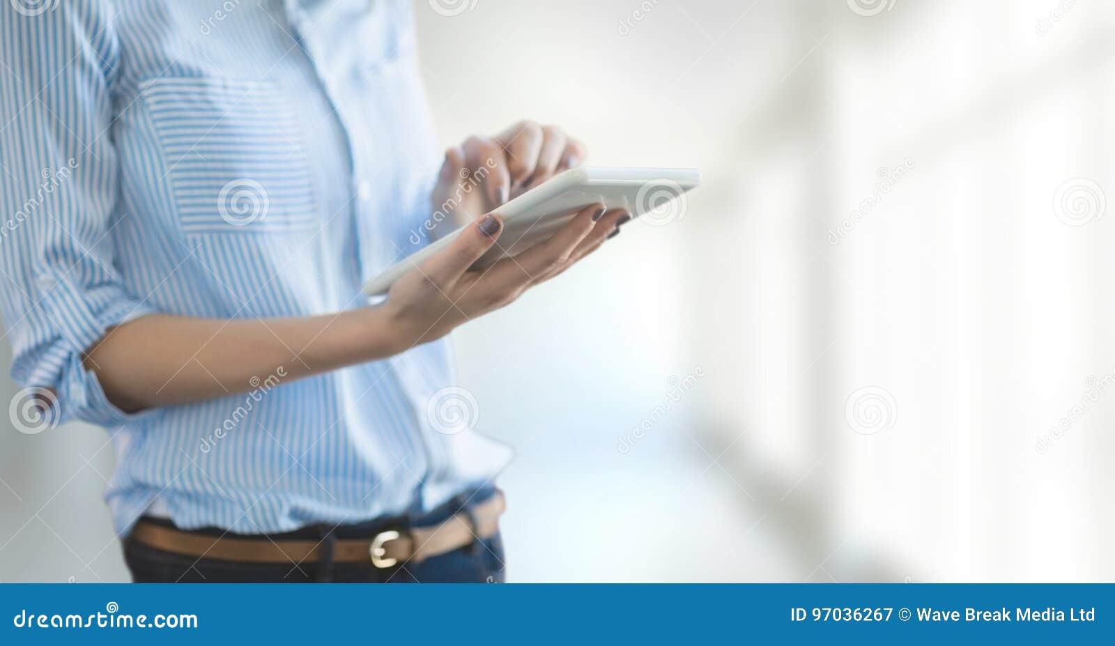 Affärskvinna som använder en minnestavla mot vit suddig bakgrund
