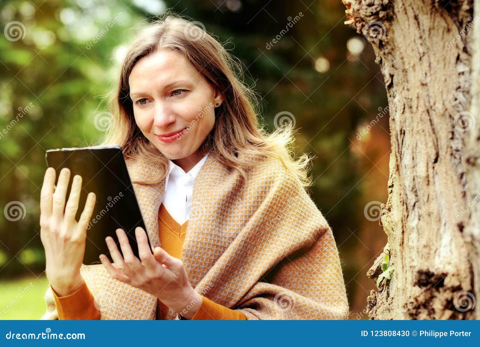 Affärskvinna som använder minnestavlan på avbrott i höst