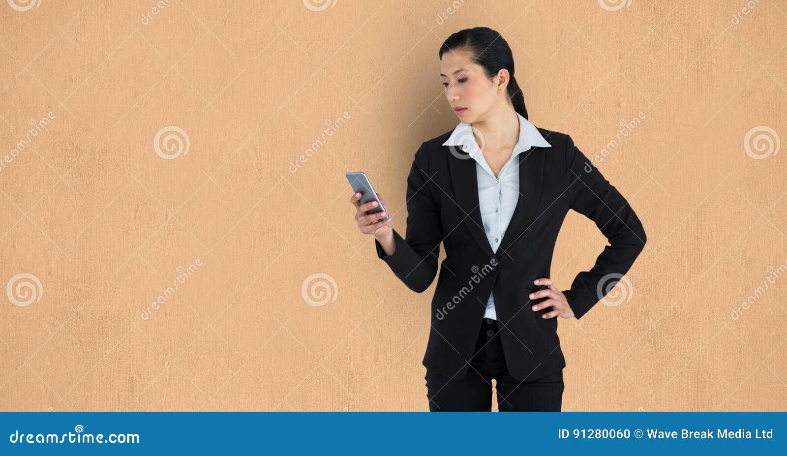 Affärskvinna som använder mobiltelefonen över beige bakgrund