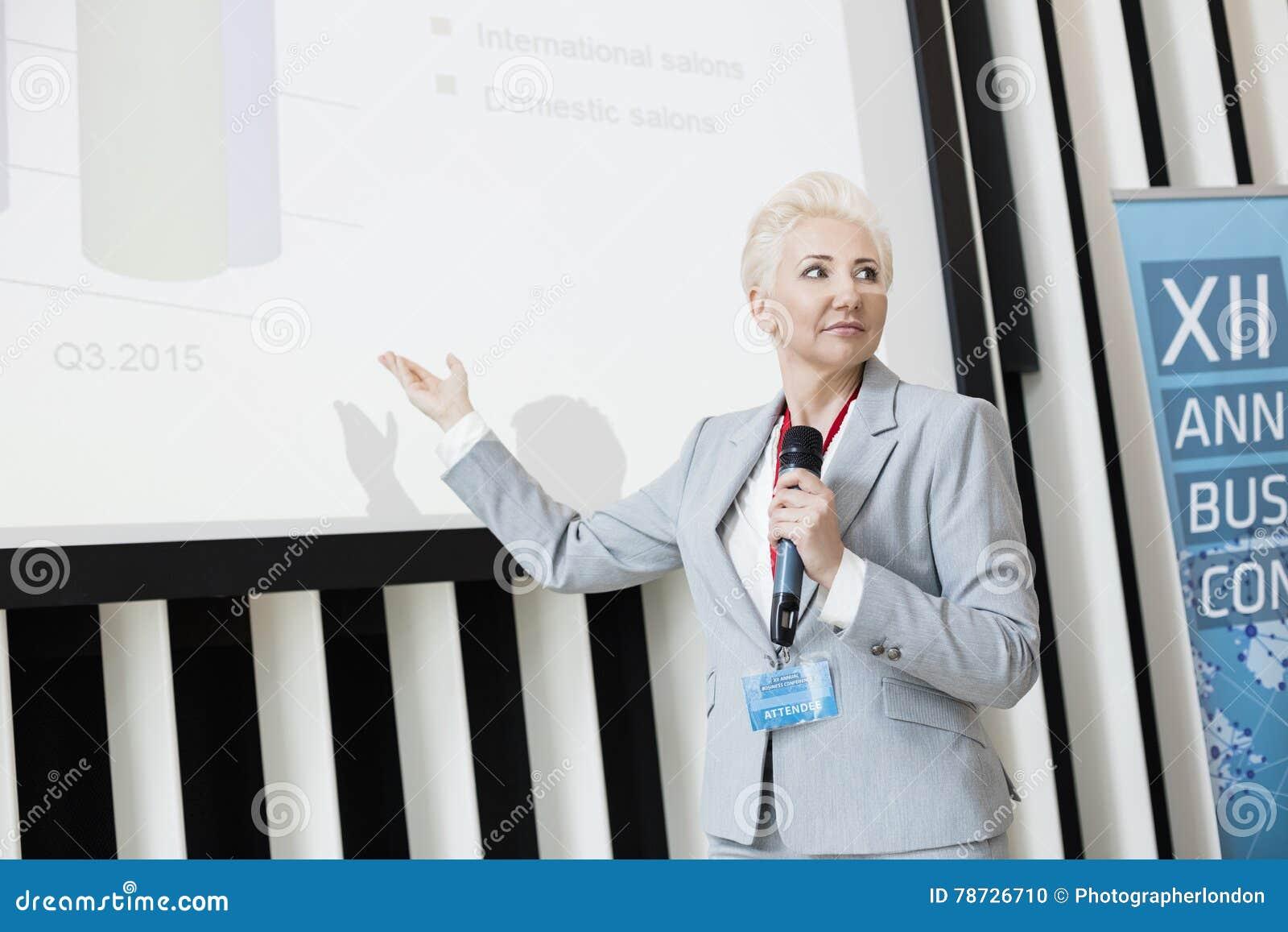 Affärskvinna som förklarar strategi på projektionsskärmen på konventcentret