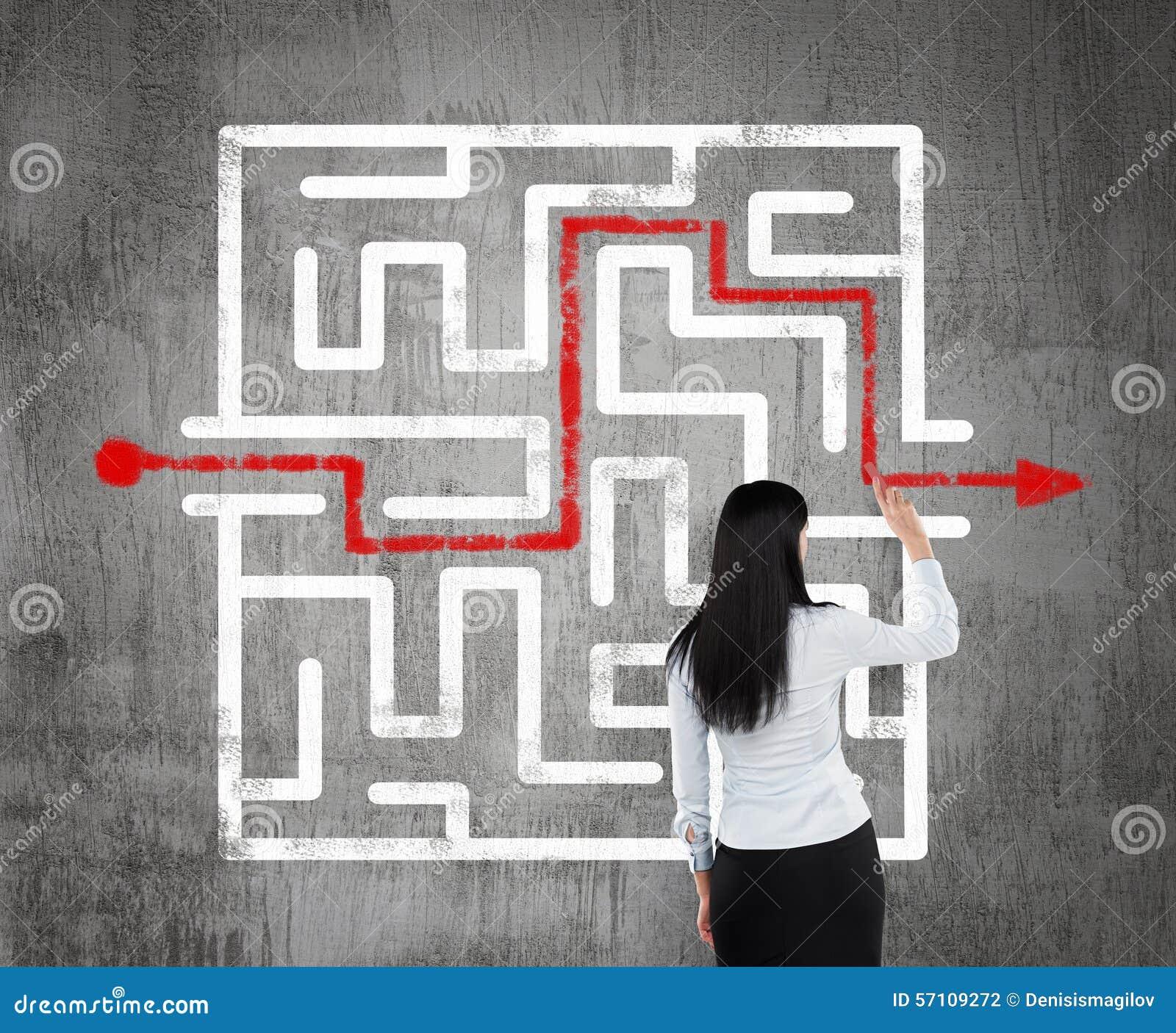 Affärskvinna som finner lösningen av en labyrint