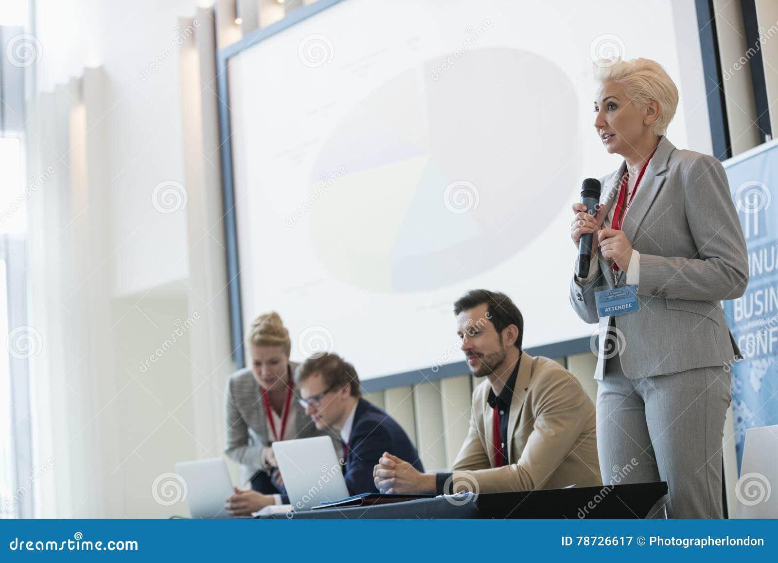 Affärskvinna som ger presentation i seminariumkorridor