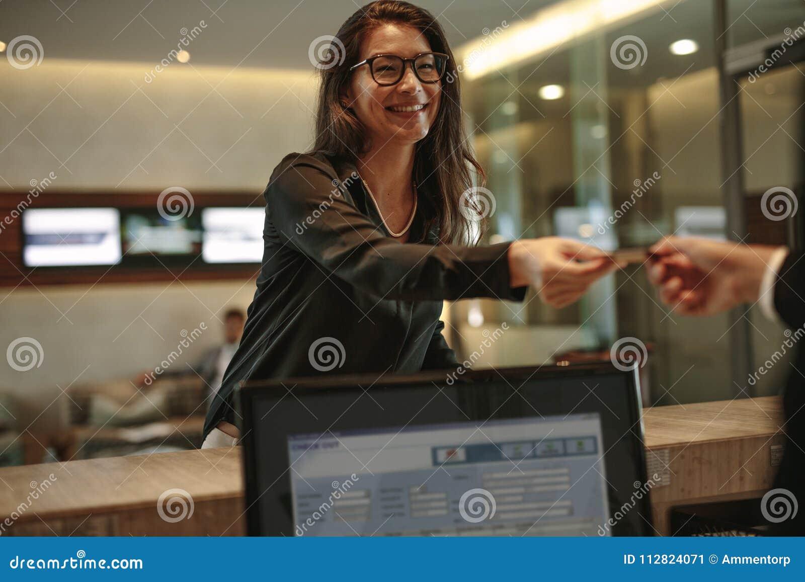 Affärskvinna som mottar det nyckel- kortet för hotellrum