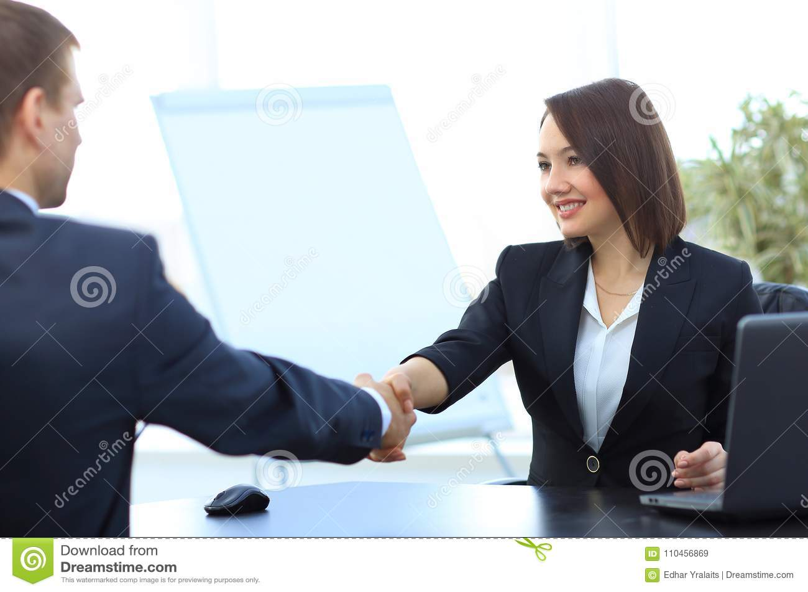Affärskvinna som skakar händer med en affärspartner över ett skrivbord