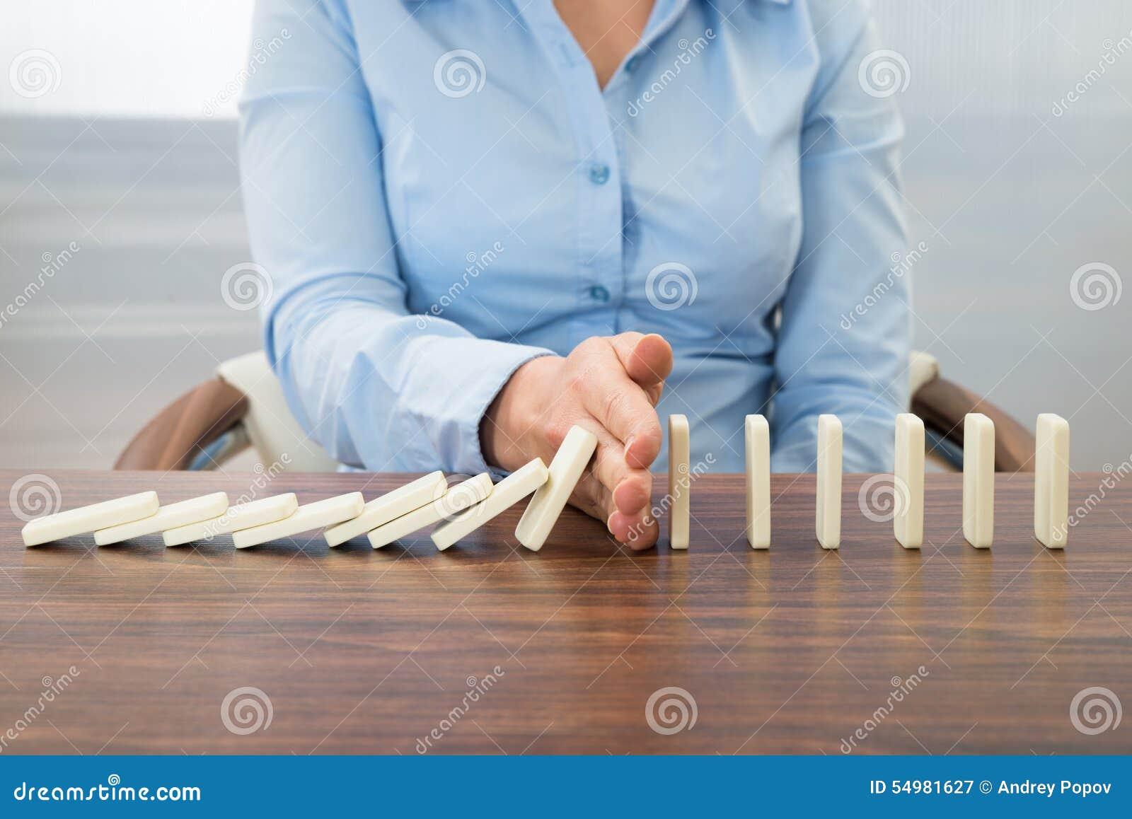 Affärskvinna som stoppar effekten av dominobricka