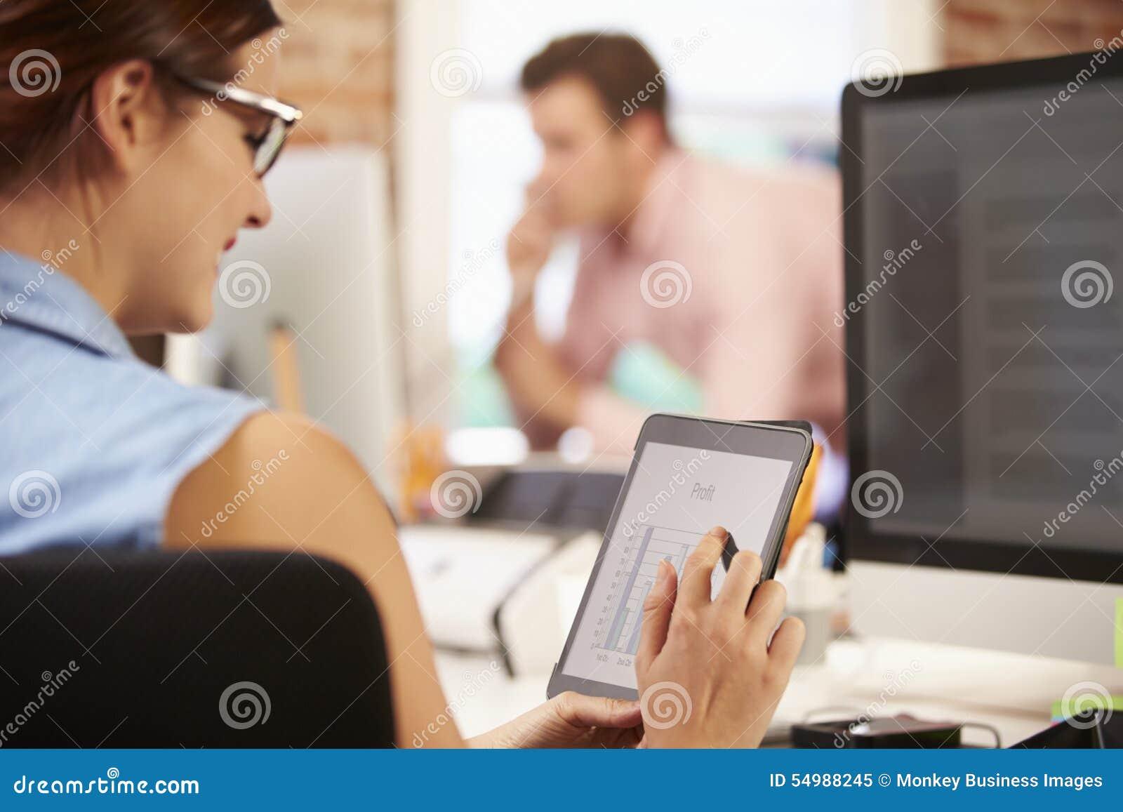 Affärskvinna Using Digital Tablet i idérikt kontor