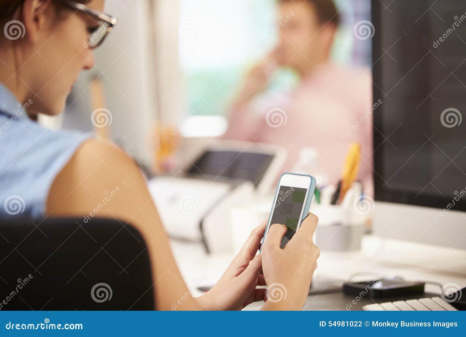 Affärskvinna Using Mobile Phone i idérikt kontor