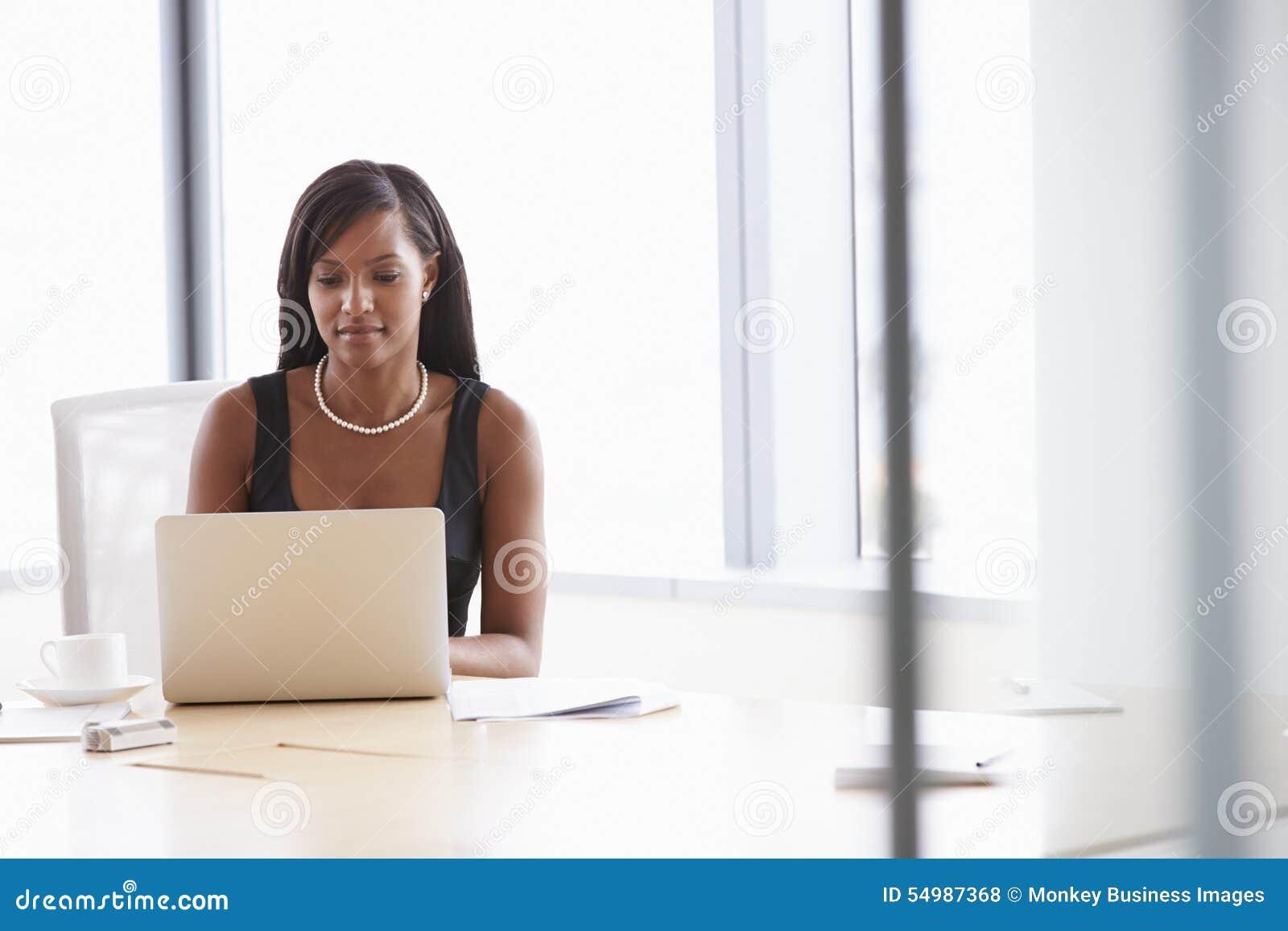 Affärskvinna Working On Laptop på styrelsetabellen