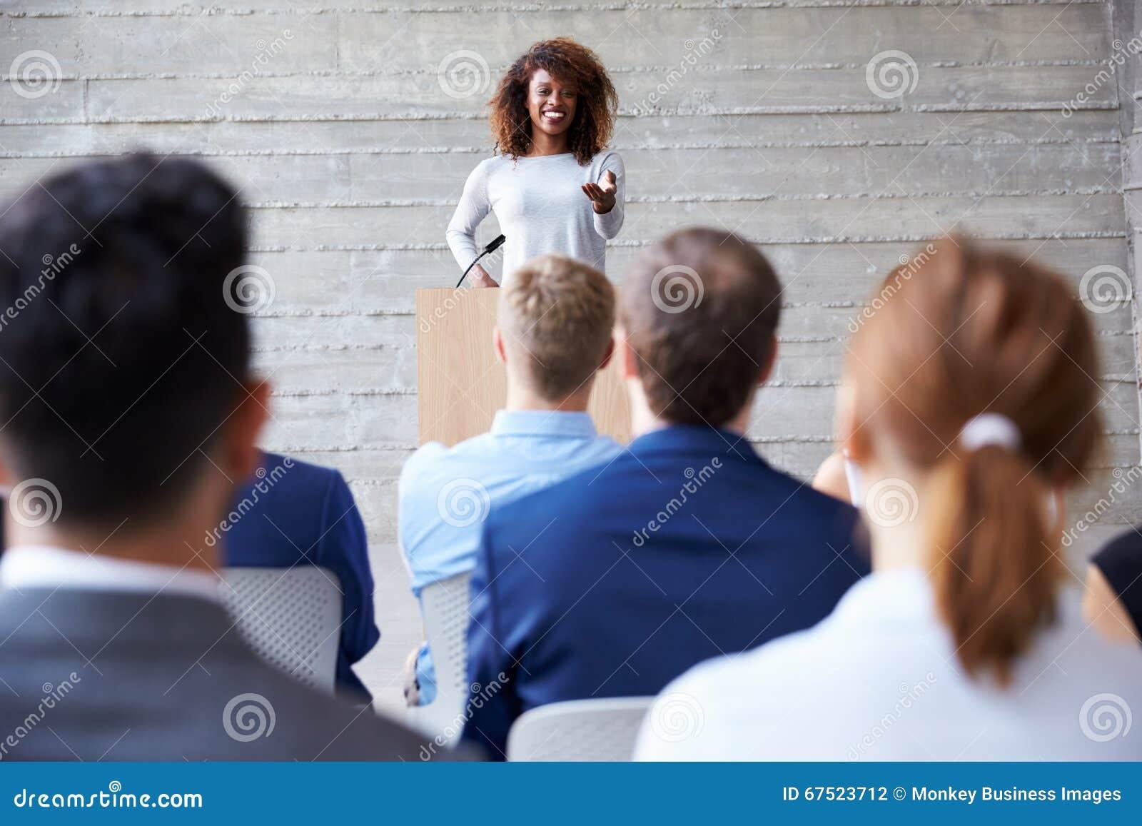 AffärskvinnaAddressing Delegates At konferens