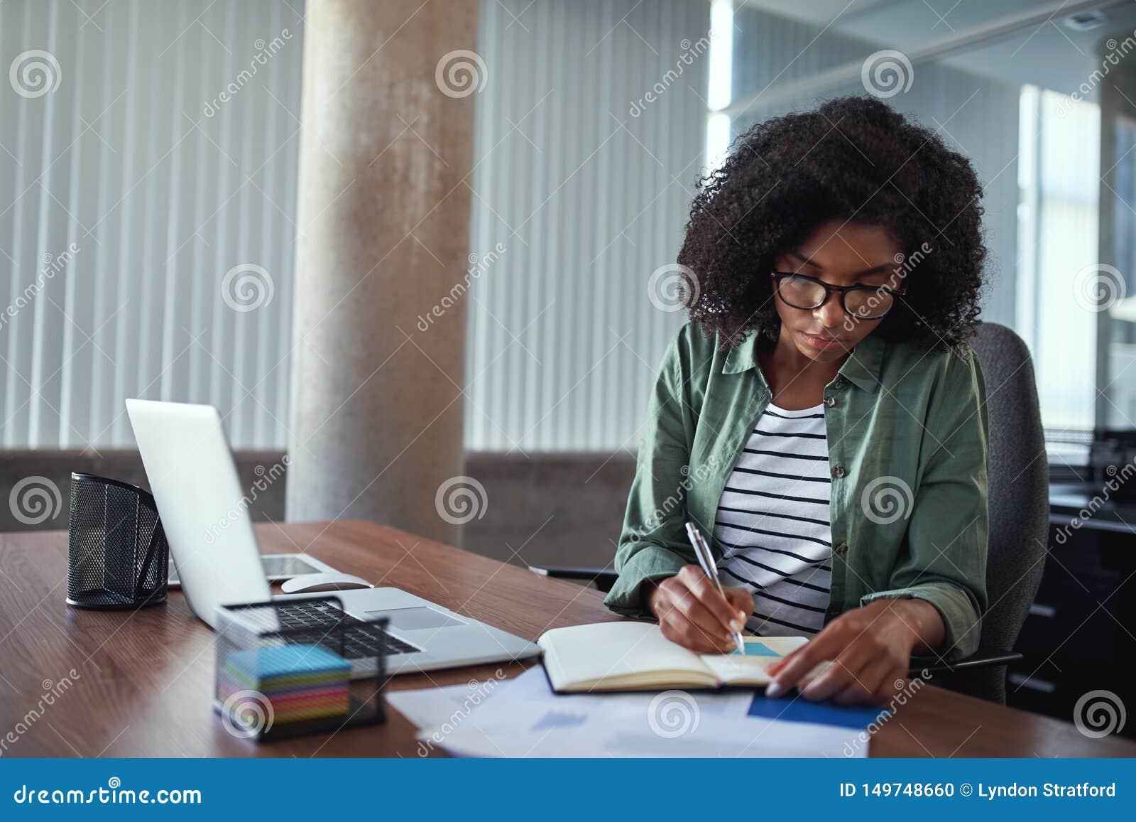 Affärskvinnahandstil i en dagordning på ett skrivbord på kontoret