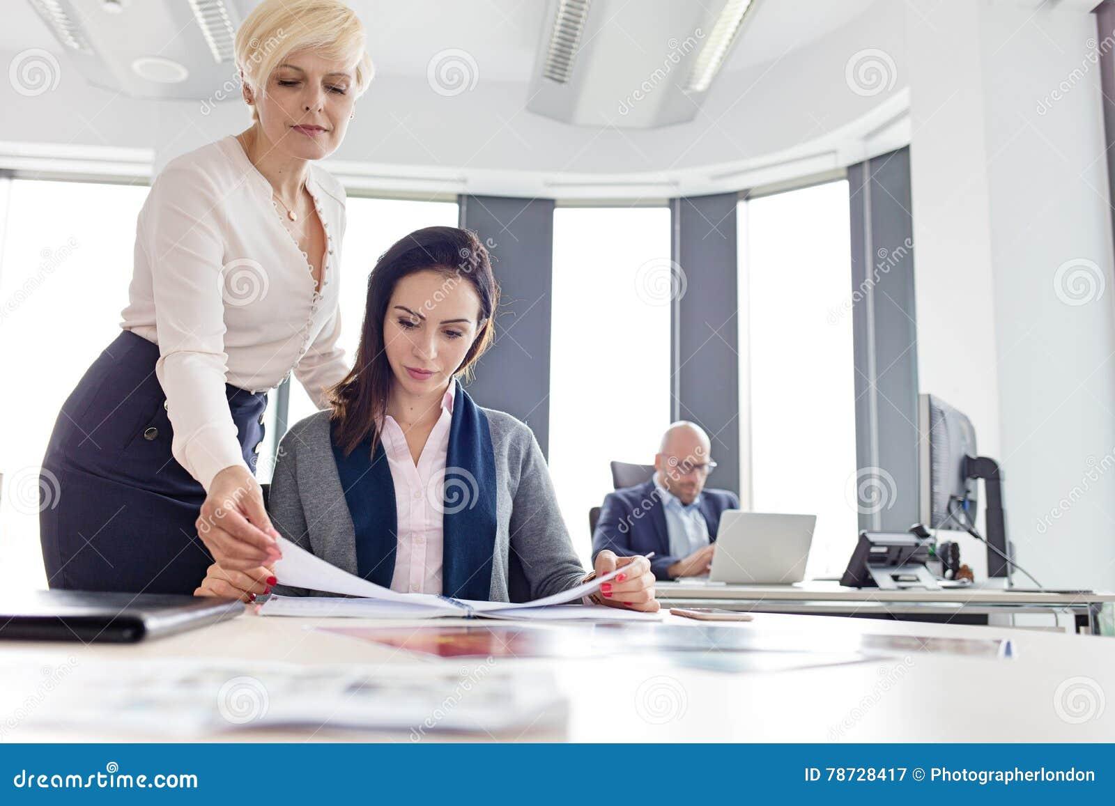 Affärskvinnaläsebok med den manliga kollegan i bakgrund på kontoret