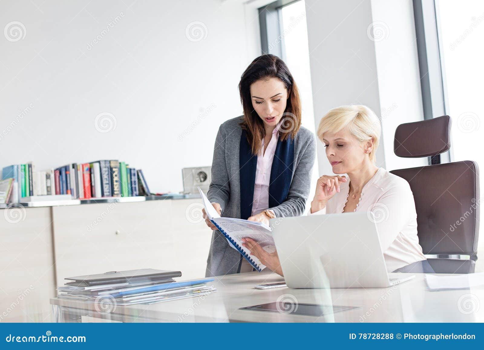 Affärskvinnaläsebok på skrivbordet i regeringsställning
