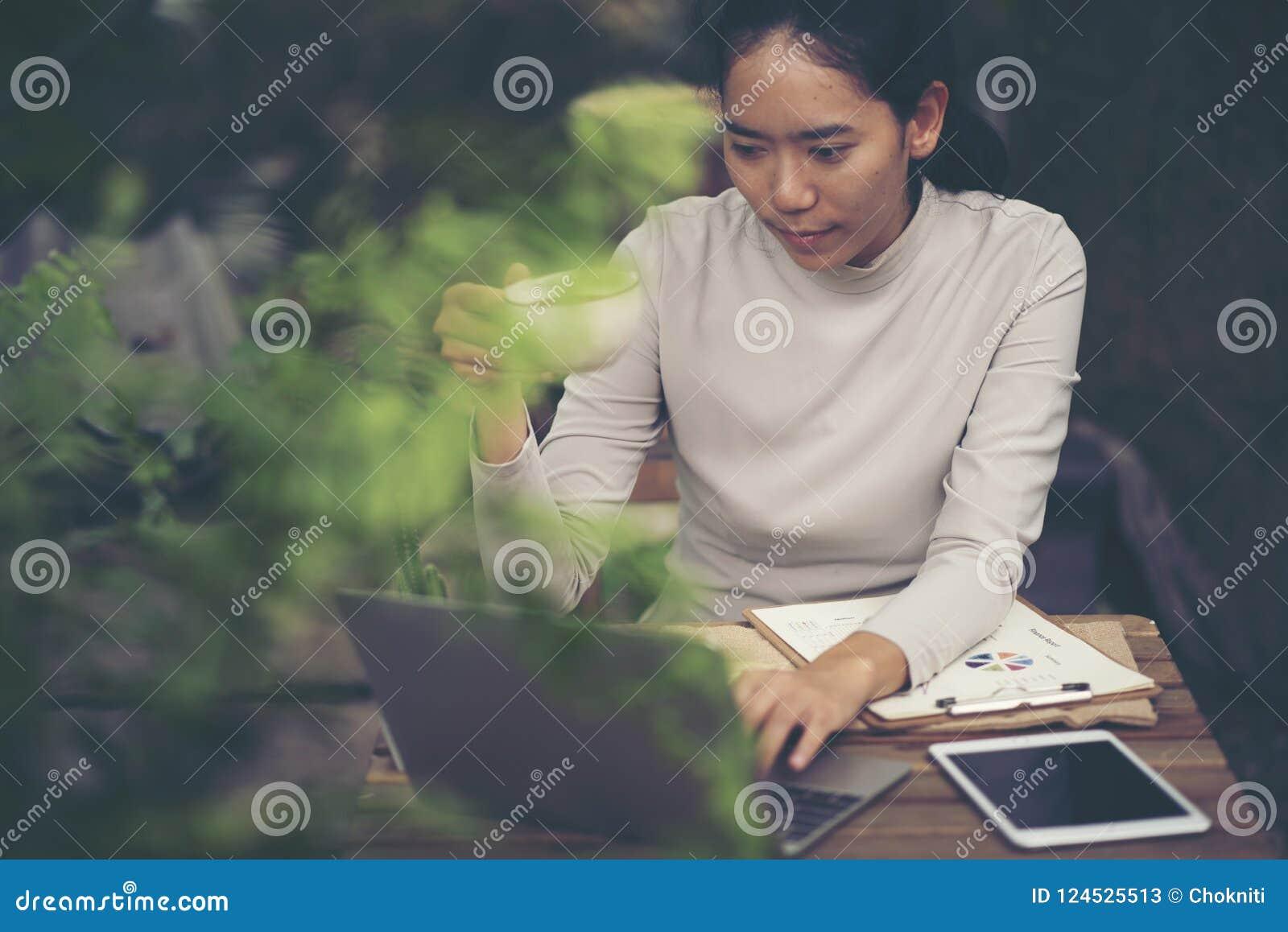 Affärskvinnamaskinskrivning på bärbara datorn på arbetsplatskvinnan som arbetar i hom
