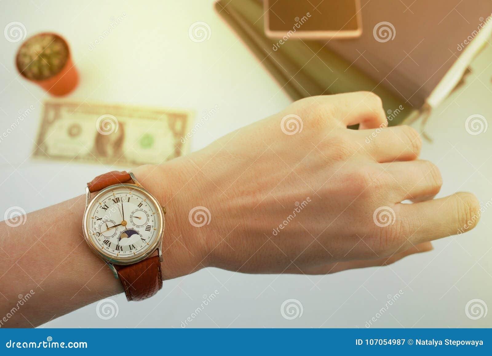 Affärskvinnan ser klockan på hennes handled, över en vit tabell som pengar och dagböcker ligger på