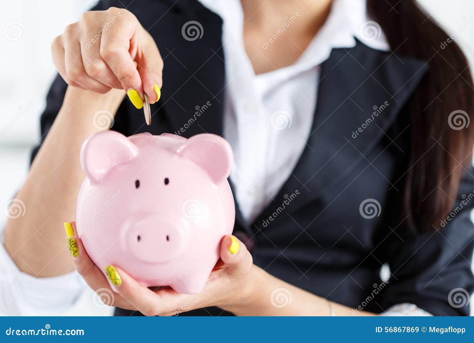 Affärskvinnan som sätter mynt för stiftpengar in i rosa piggybank, placerar