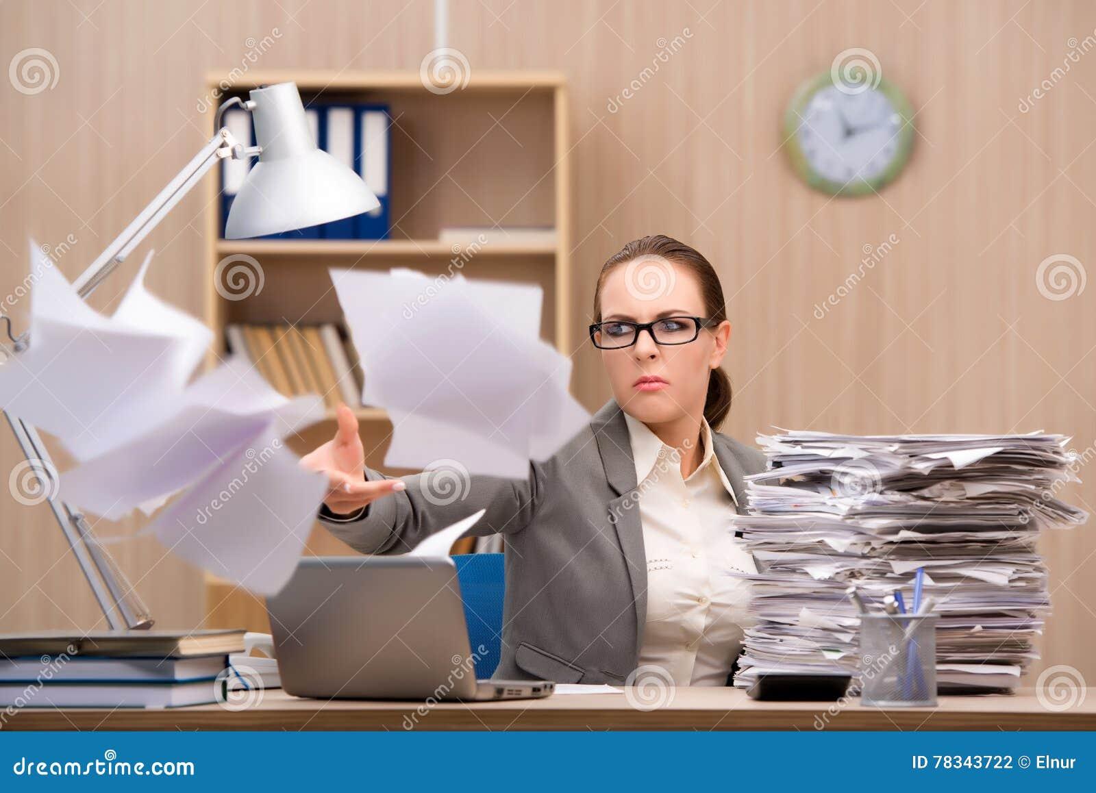 Affärskvinnan under spänning från för mycket arbete i kontoret