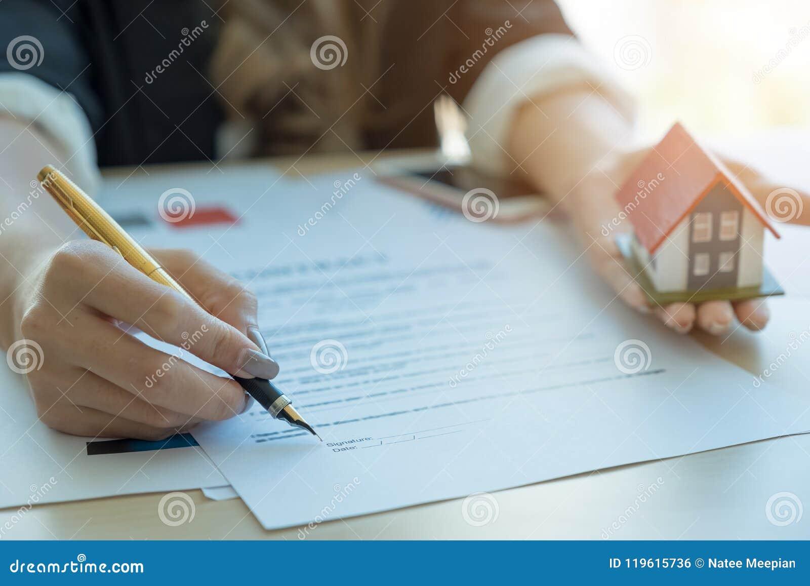 Affärskvinnan undertecknar avtal och hållande hoouse arkitektoniskt M
