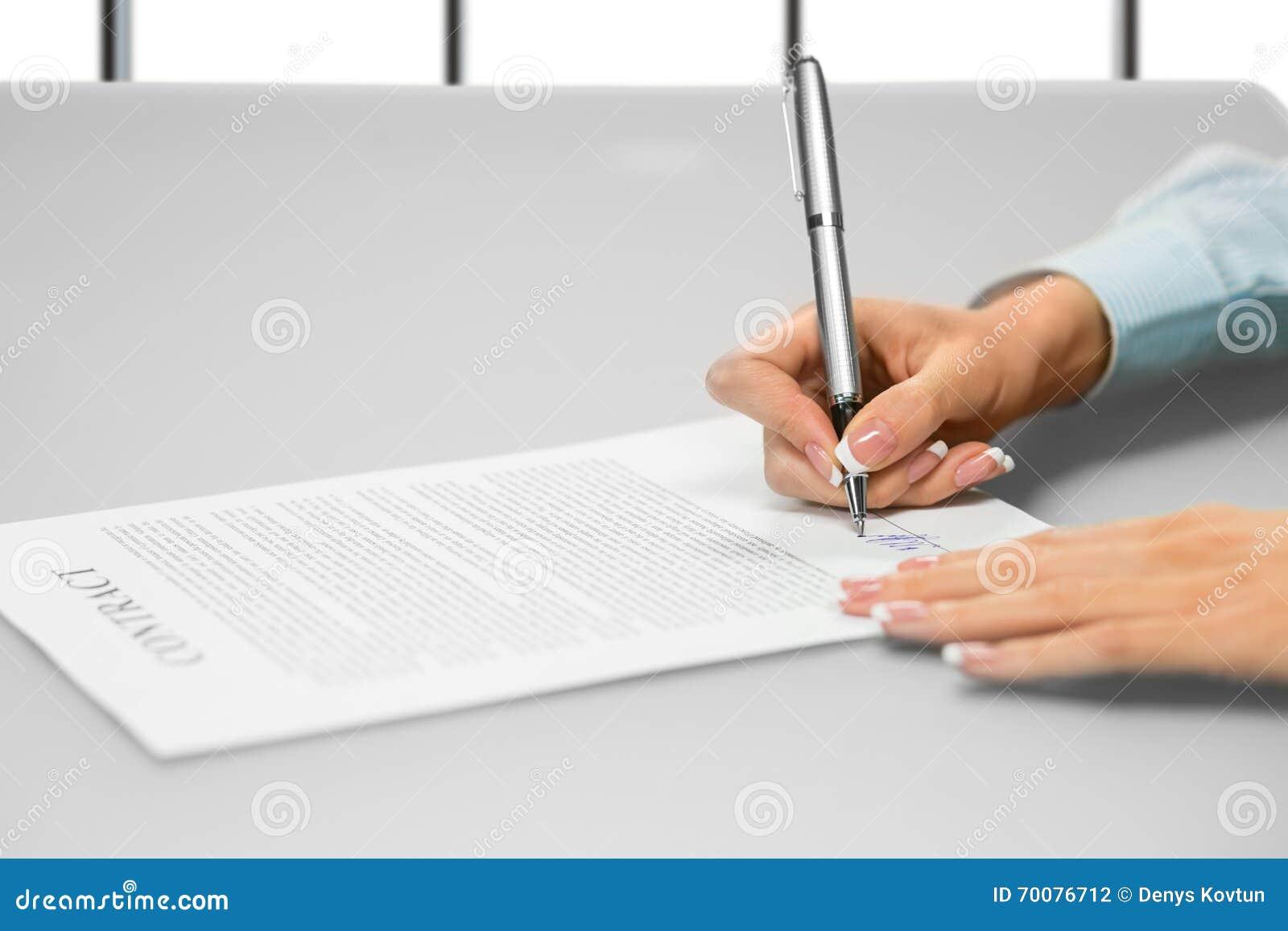 Affärskvinnans hand undertecknar ett dokument