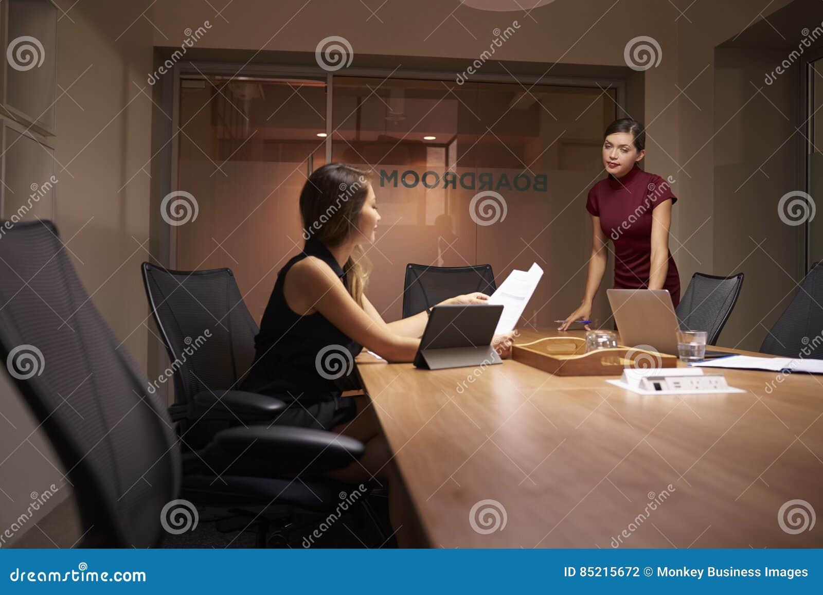Affärskvinnaställningar som talar till kollegan som sent arbetar