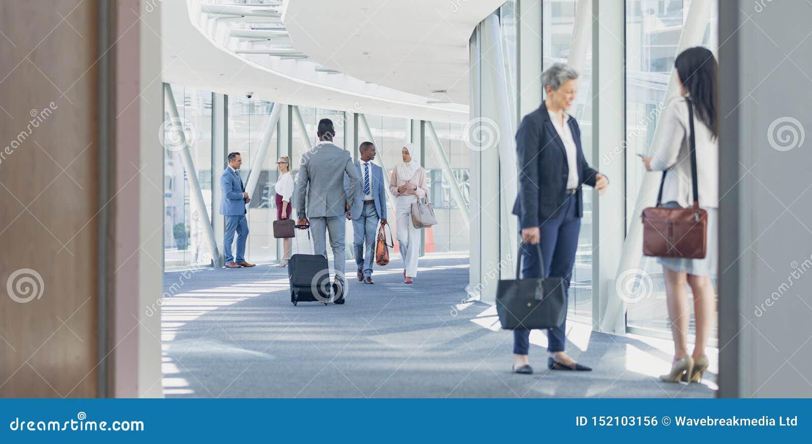 Affärskvinnor som påverkar varandra med de i korridor